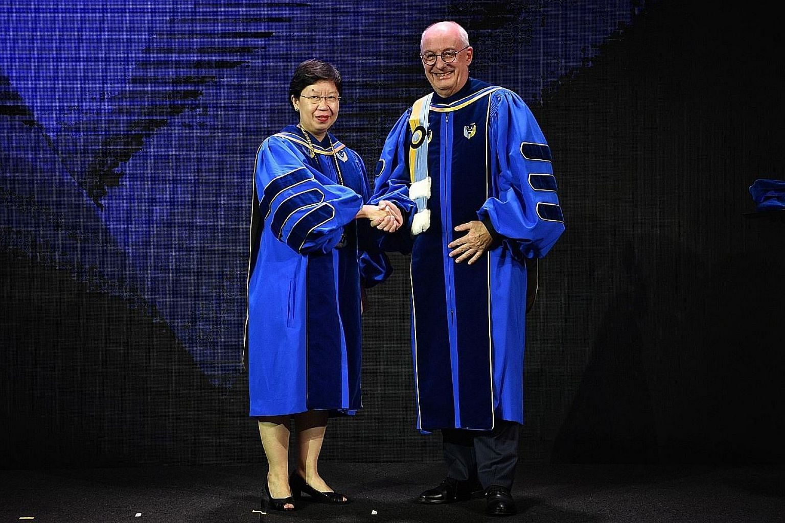 Singapore Management University's outgoing president Arnoud De Meyer and his successor, SMU provost Lily Kong, at a farewell ceremony for the 64-year-old don last night.