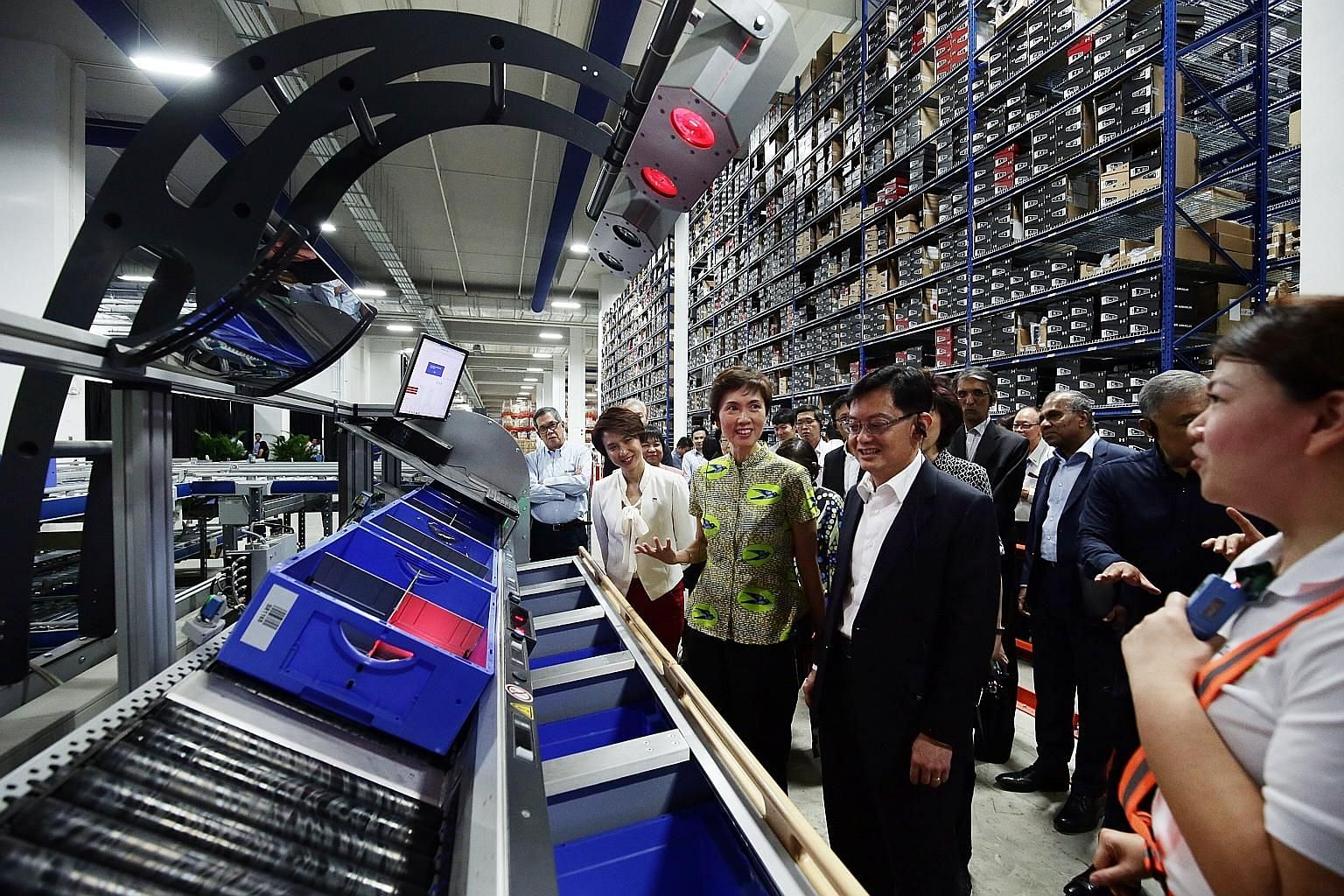 Finance Minister Heng Swee Keat (foreground), who chairs the Future Economy Council, with fellow council members, including Manpower Minister Josephine Teo and Senior Parliamentary Secretary Low Yen Ling, on a tour of the SingPost Regional eCommerce