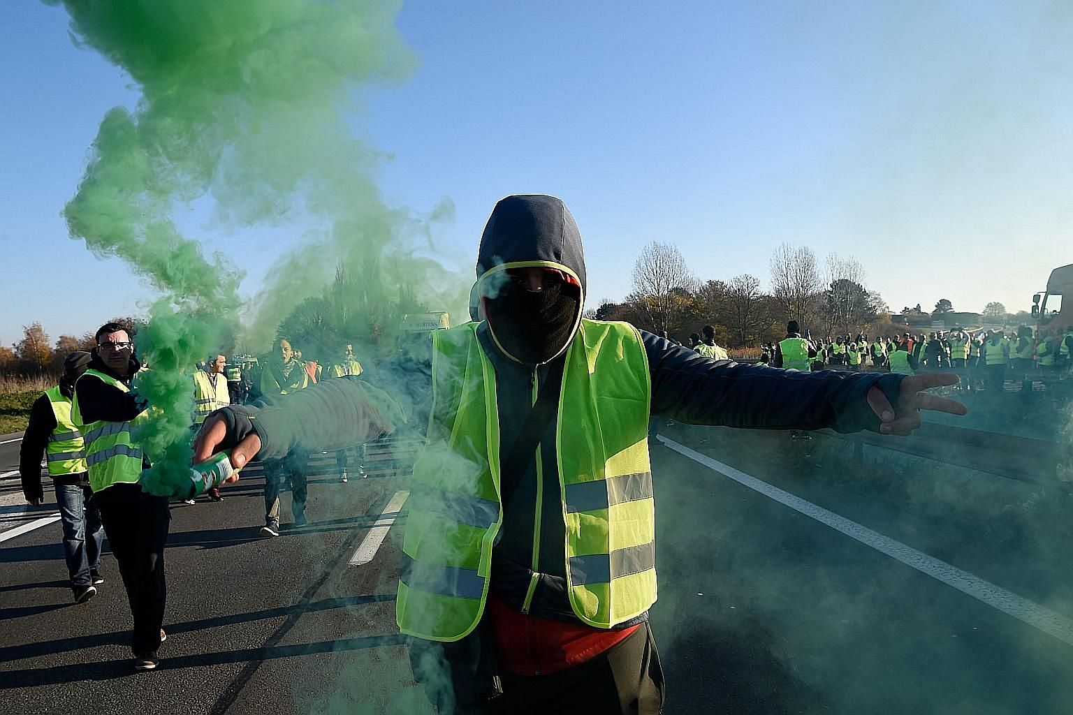 """A man protesting against higher fuel taxes in France yesterday. Those taking part in the """"yellow vest"""" blockade caused logjams on highways and blocked roundabouts as they railed against the tax hikes introduced by President Emmanuel Macron."""