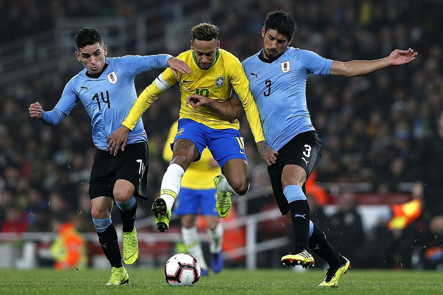 Brazil striker Neymar finding himself sandwiched between Uruguay's Lucas Torreira (left) and Bruno Mendez during their friendly at London's Emirates Stadium on Friday. Neymar scored from the penalty spot for his 60th international goal.