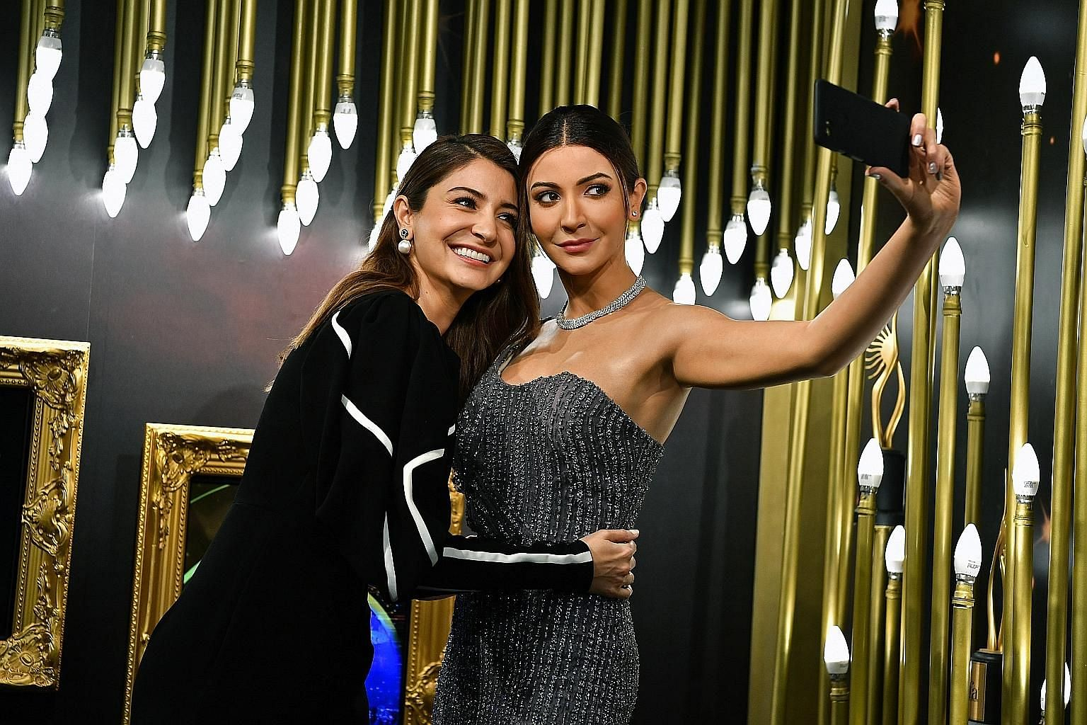 Actress Anushka Sharma (left) with her wax figure, who can speak and whose phone can take photographs.