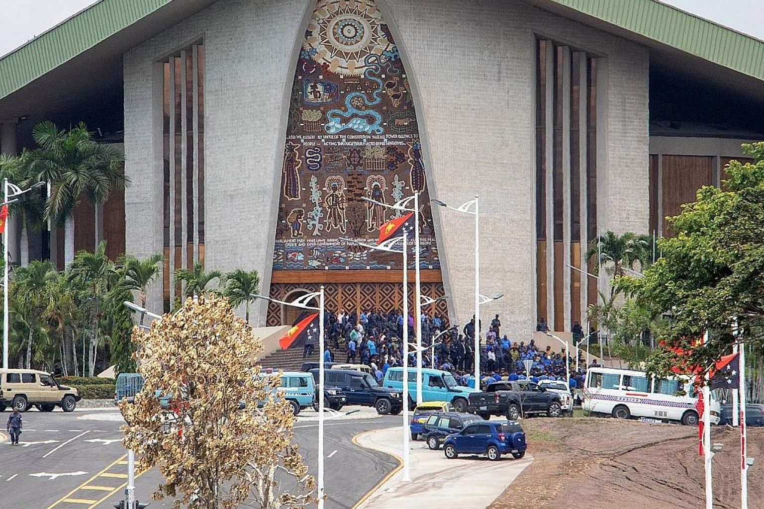 Papua New Guinea police and soldiers (above) outside the Parliament building in the capital Port Moresby yesterday. They stormed Parliament and smashed windows and furniture (below) to demand payment of the special Apec duty allowance.