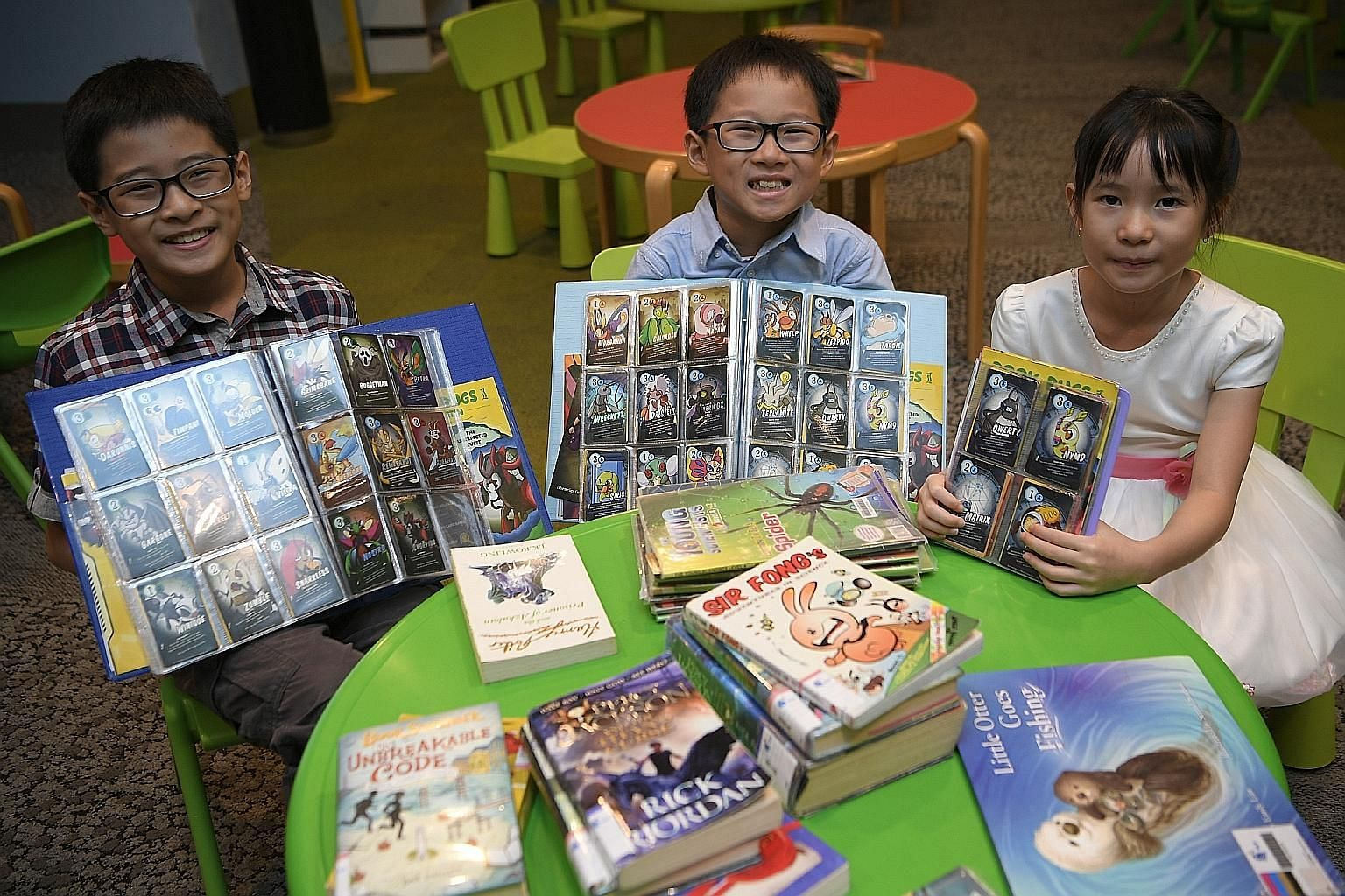 Ilika Motani, 10, and her brother, Darshan Motani, six, are avid Book Bugs card collectors. Lucian Lee, eight, and Lukas Lee, four, with their parents, Ms Chanelle Lim and Mr Larry Lee, taking part in a National Heritage Board's Heritage Explorers Pr