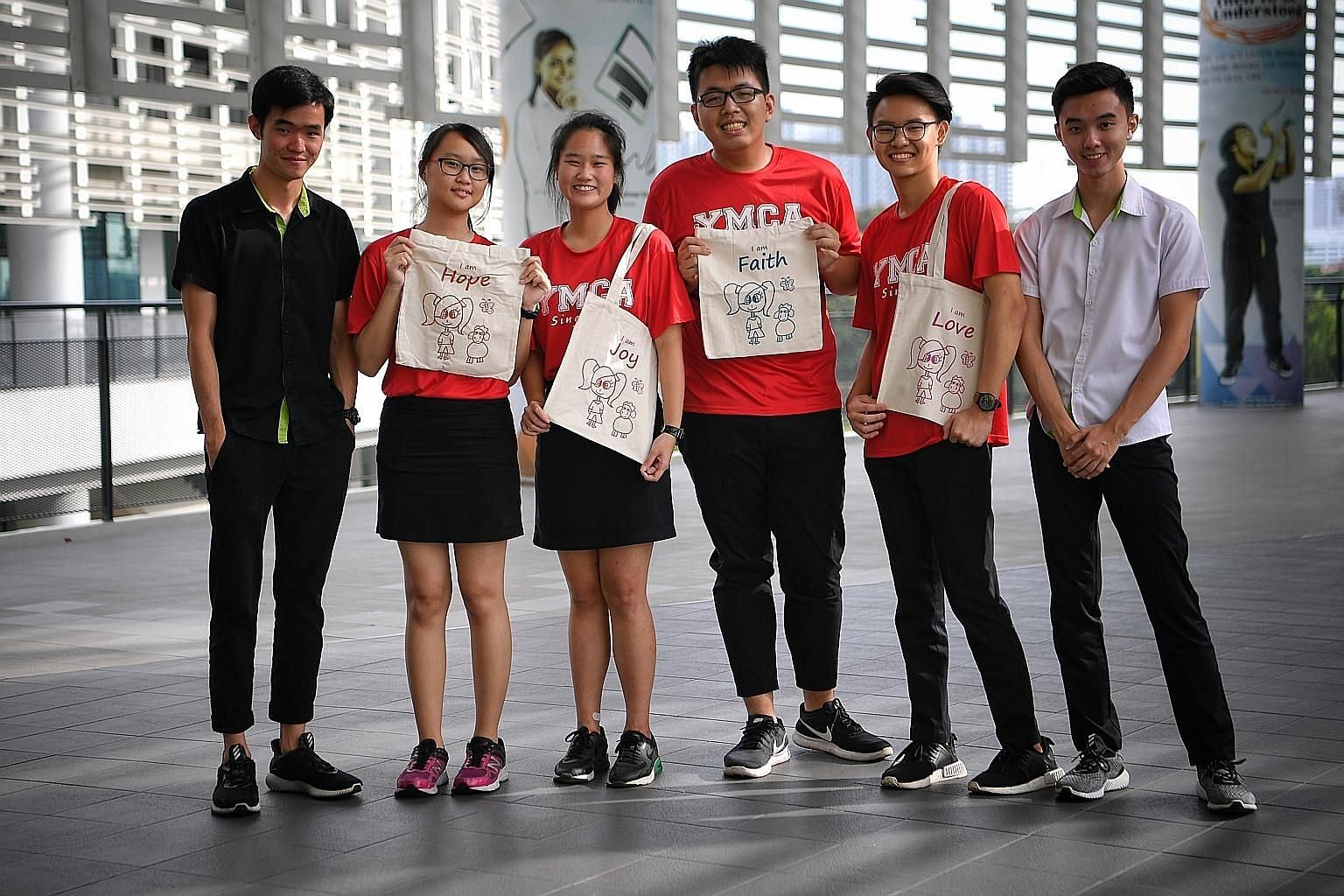 The EduTomahawk team (in red T-shirts) comprising ITE students (from second from left) Gan Shi Ying, 18; Cheryl Ee, 18; Tan Jia Shun, 19; and Josh Ang, 19, with samples of the tote bags they sold to raise funds for underprivileged children from Canos