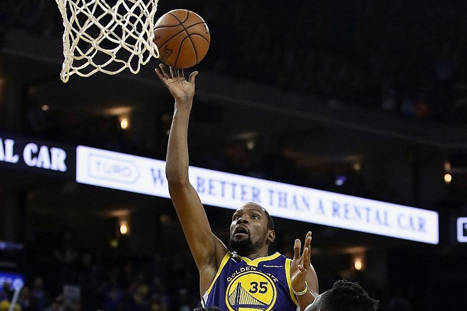 Golden State's Kevin Durant managing to take a shot despite the close attention of Orlando's Terrence Ross (No. 31) and Mo Bamba at Oracle Arena on Monday. The Warriors' 116-110 win was their third in four days after they had lost four in a row.