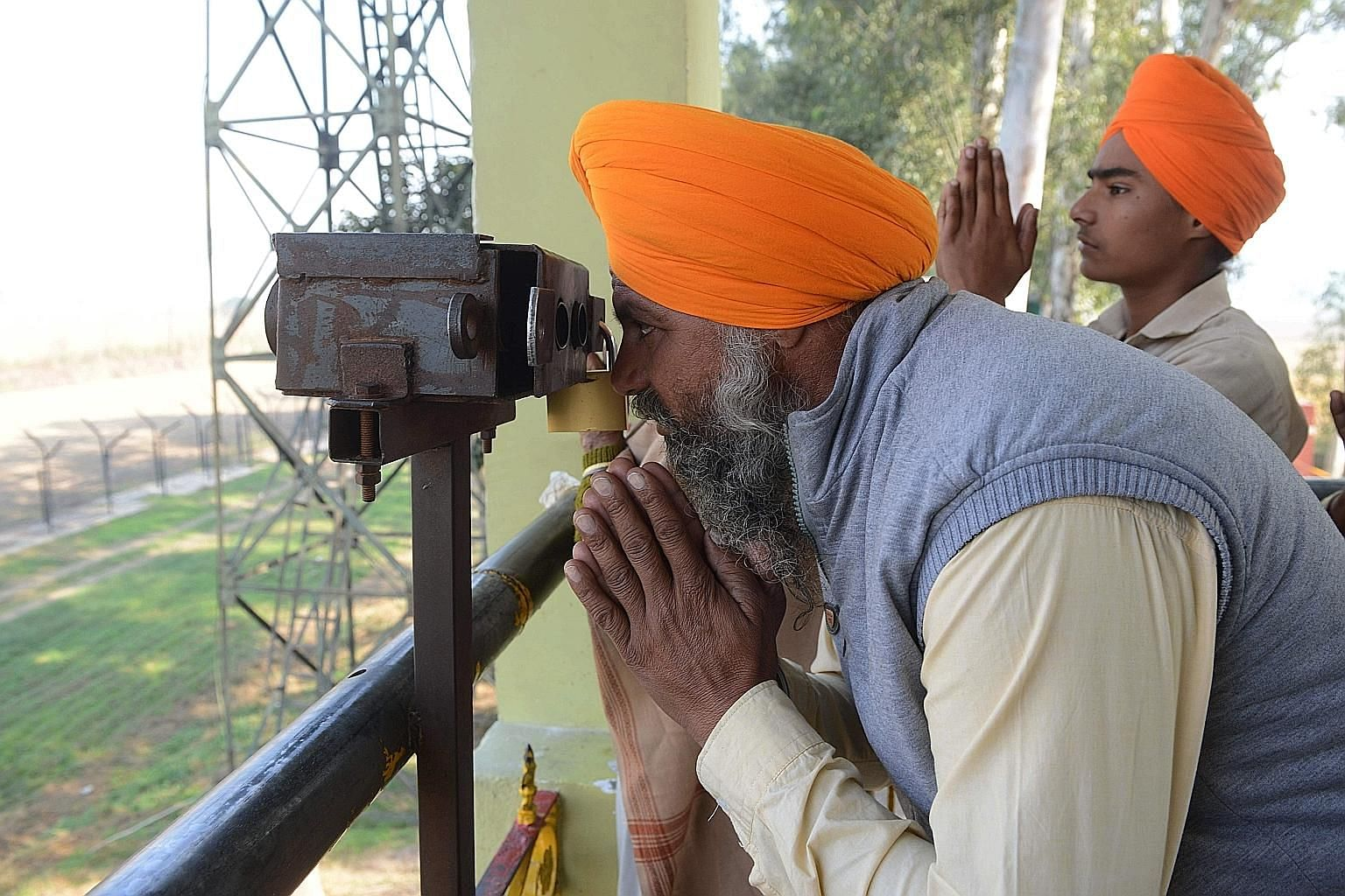 An Indian Sikh devotee looking through a pair of binoculars towards the Gurdwara Darbar Sahib in Kartarpur, Pakistan, from the Indian side at Dera Baba Nanak, on the outskirts of Amritsar, on Sunday.