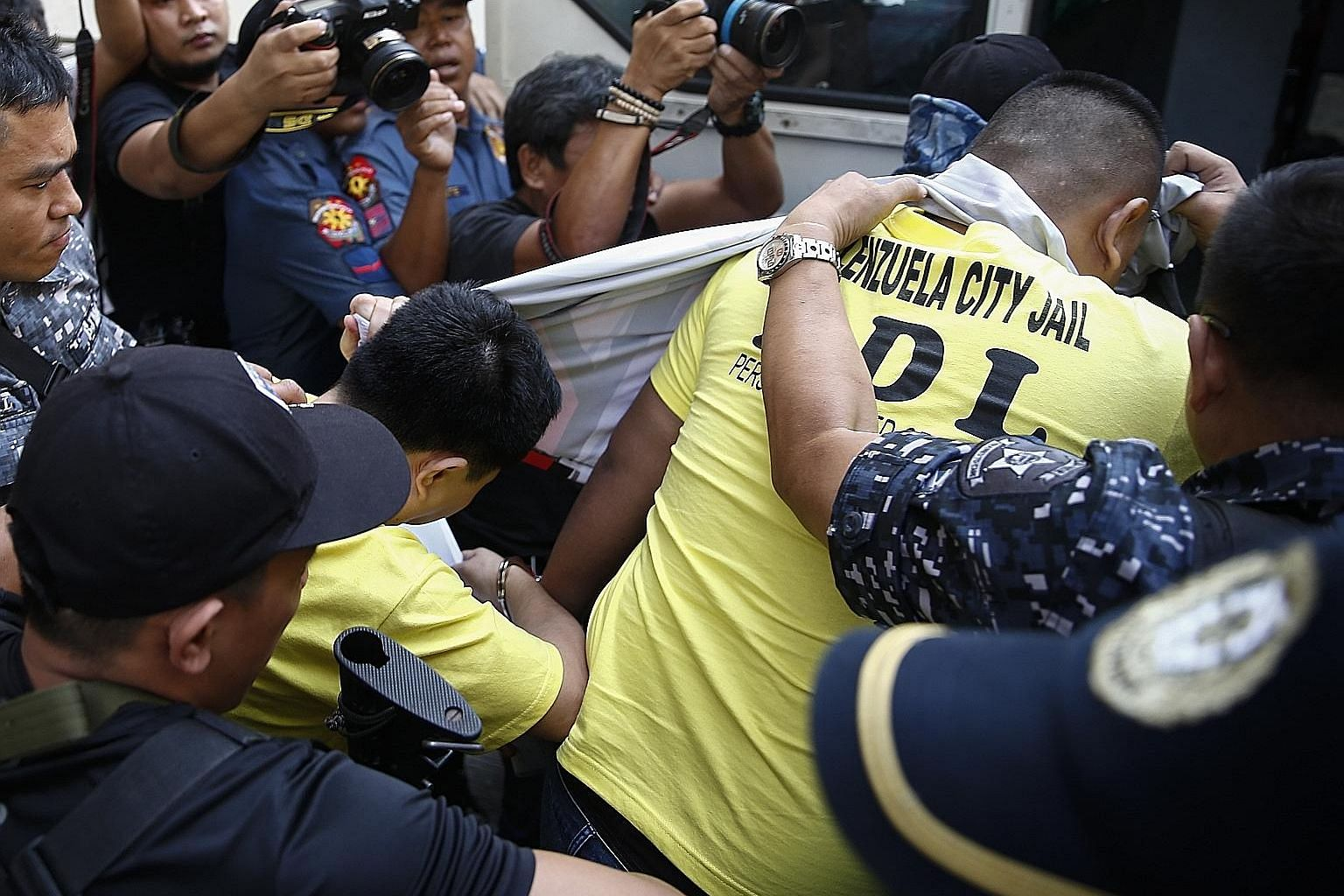 Two of the police officers (below, in yellow) convicted of the murder of teen Kian delos Santos (left) being taken out of a Caloocan city court building yesterday.