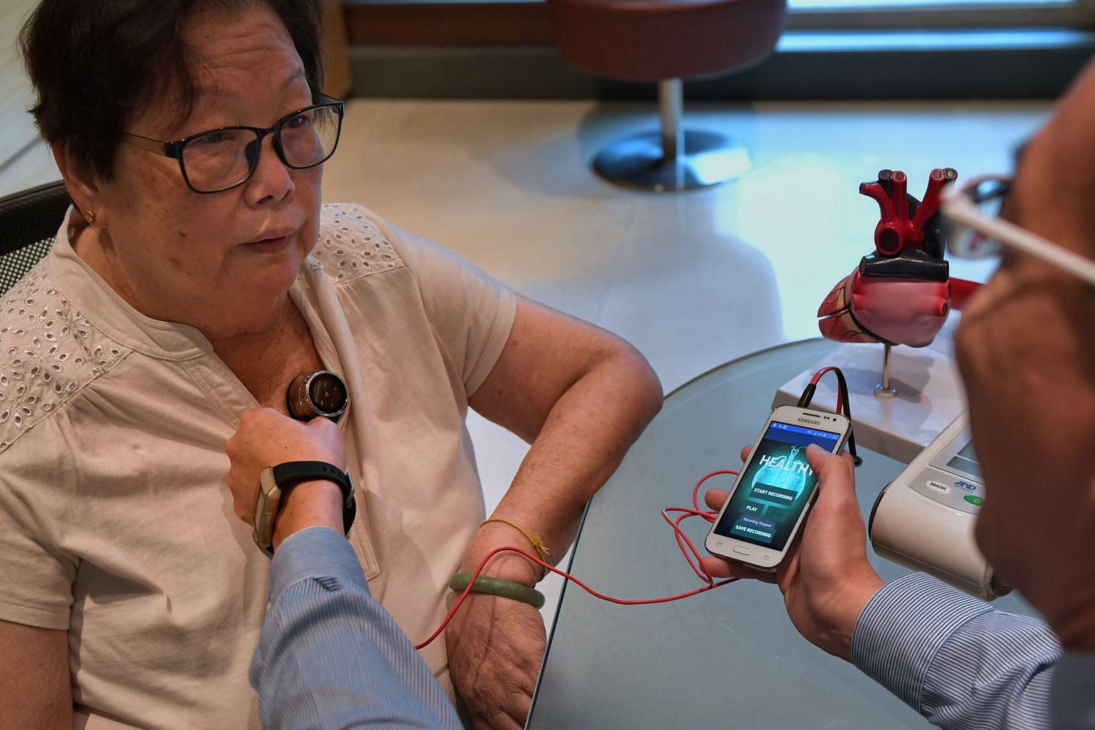 Tan Tock Seng Hospital's head of cardiology David Foo demonstrating the use of the device - which checks for fluid accumulation in the lungs, an early symptom of heart failure - to heart patient Tan Hui Keng at the hospital yesterday. The device was