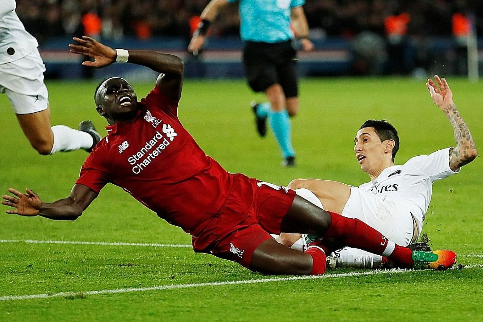Paris Saint-Germain's Angel di Maria (in white) fouling Liverpool's Sadio Mane during their Champions League clash on Wednesday. James Milner scored the resulting penalty in first-half added time to pull a goal back. It was not enough though, as PSG'
