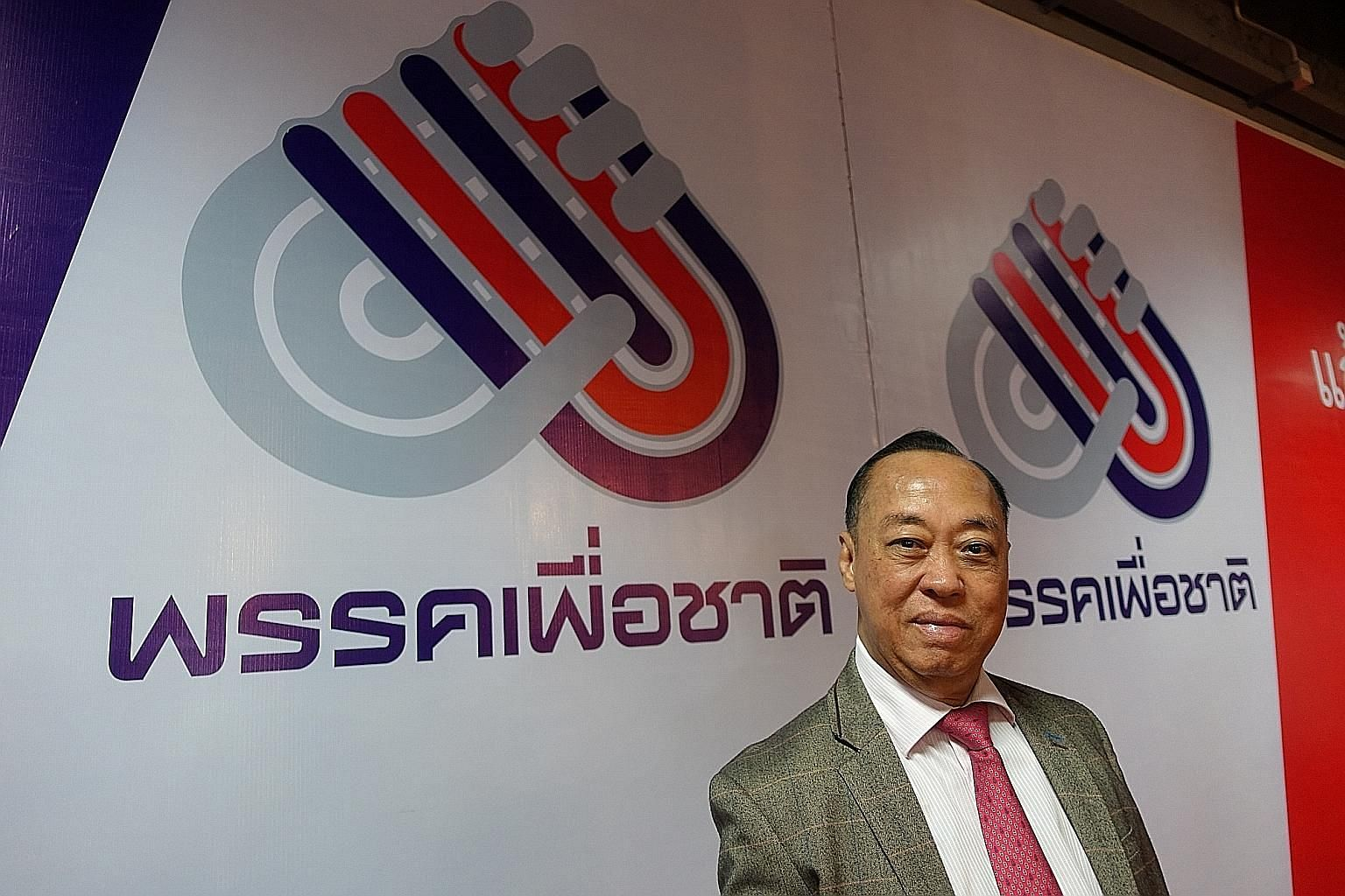 Mr Songkram Kitlertphairoj, leader of Thailand's Pheu Chart Party, in front of his party's logo.