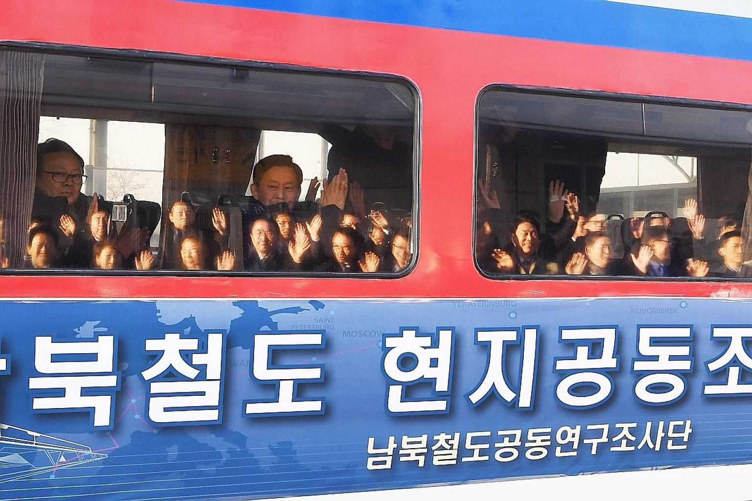 Left: Members of a South Korean delegation waving as they headed to the North for a landmark joint inspection of its railways yesterday. Above: South Korean soldiers opening the gate at the demilitarised zone for the train to pass into the North.