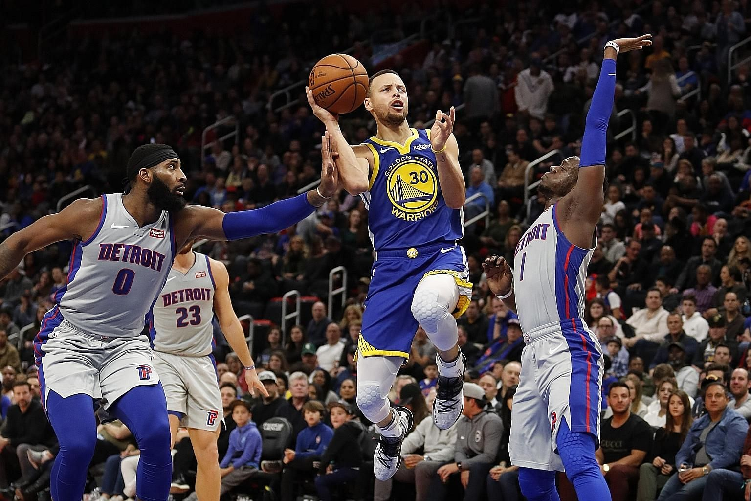 Above: Detroit Pistons forward Blake Griffin, who had a team-high 26 points, being feted by teammates after the hosts' 111-102 victory over Golden State Warriors on Saturday. Left: Stephen Curry attempting a shot, as centre Andre Drummond (No. 0) and