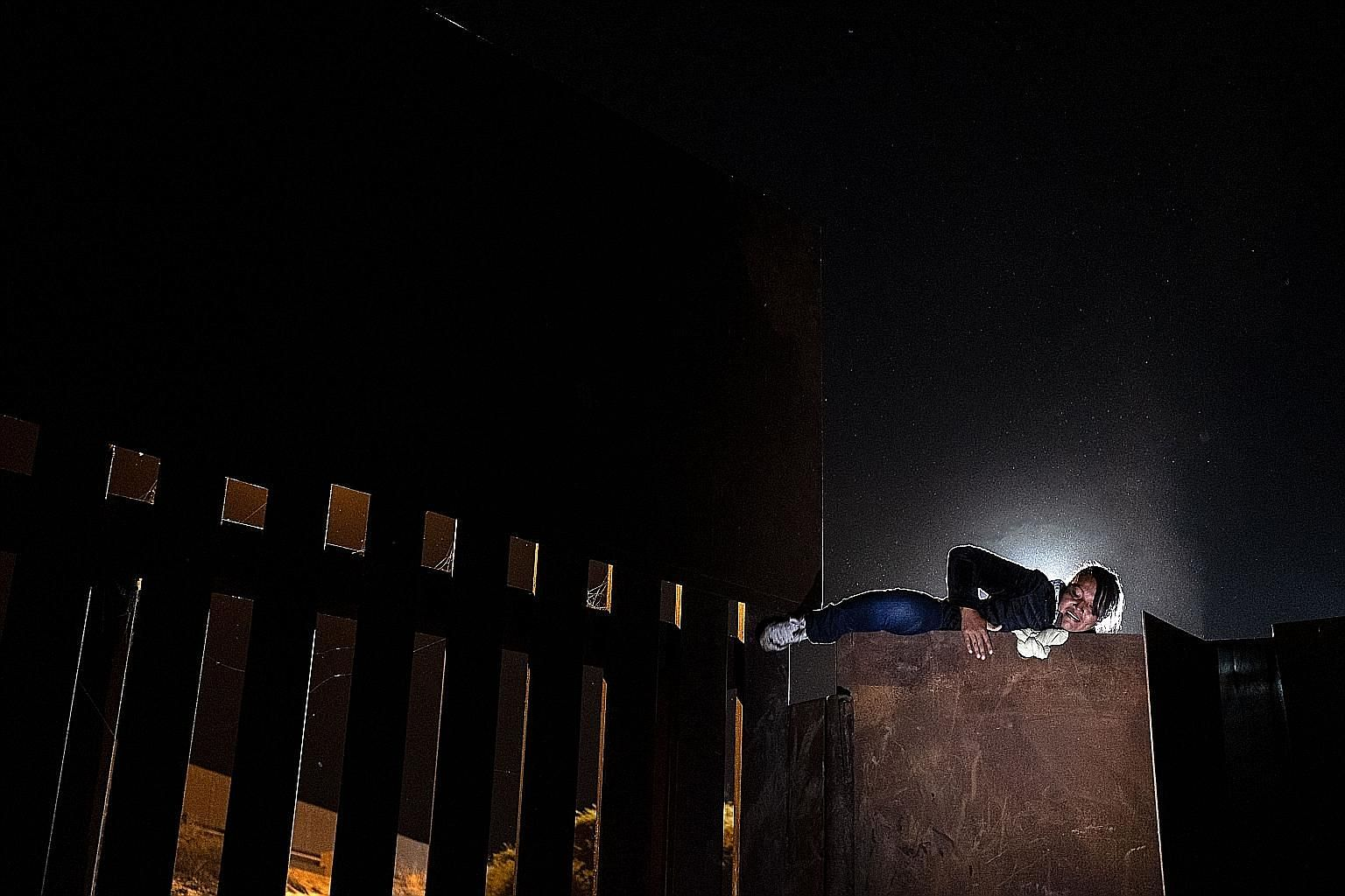 A woman who was part of a caravan of Central American migrants hoping to enter the United States climbing the metal barrier along the US-Mexico border in Playas de Tijuana, Mexico, on Monday.