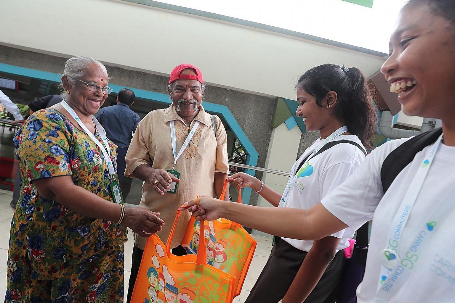 """Madam Veerama Suppiah, 77, and her husband Paraman Nayar, 76, receiving goodie bags from Pioneer Junior College students Preshika Das and Dian Haziqah, both 17. Care Ride @ South West wants to """"provide opportunities for younger commuters to better un"""