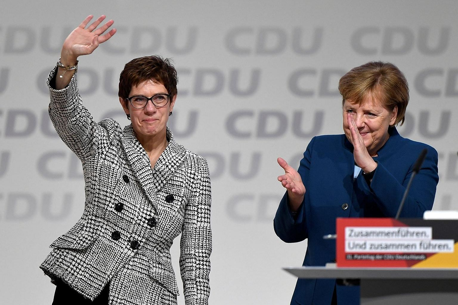 An elated Annegret Kramp-Karrenbauer waving next to German Chancellor Angela Merkel after being elected as the party leader during the Christian Democratic Union party congress in Hamburg, Germany, yesterday.