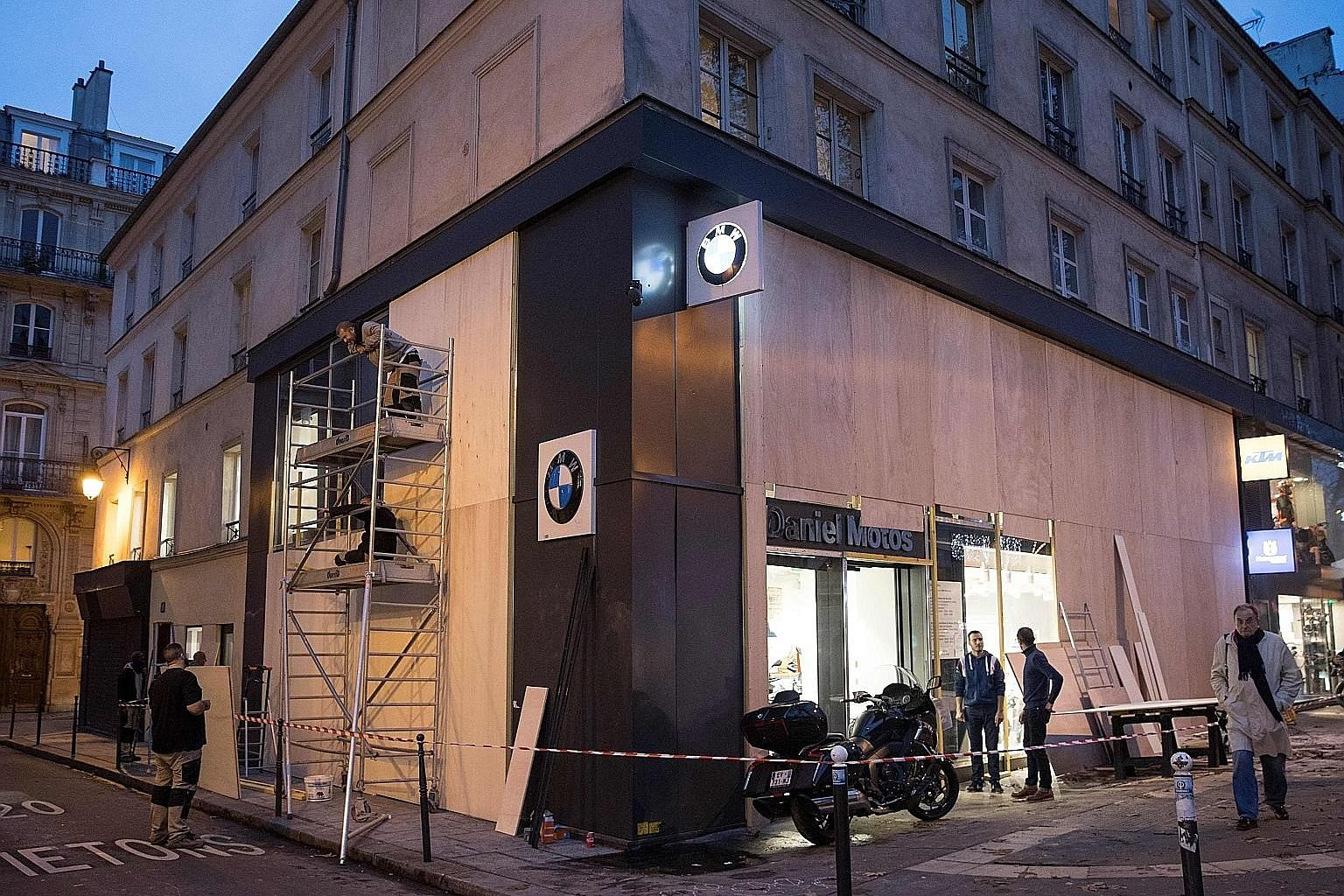 """Workers setting up wood panels to protect shop windows near Bastille Place in Paris yesterday. The authorities there have ordered today's closure to stave off another wave of violent """"yellow vest"""" protests over living costs."""