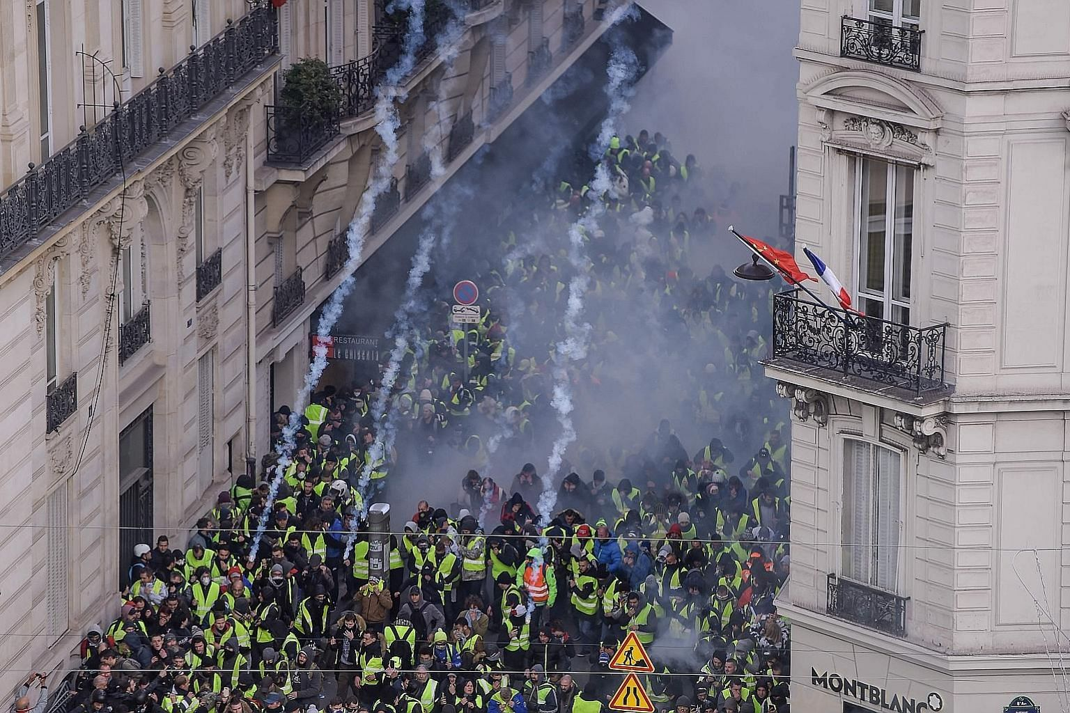 Protesters clashing with riot police as tear gas filled the air on the Champs-Elysees in Paris yesterday. An estimated 31,000 people had joined the protests, Deputy Interior Minister Laurent Nunez said.