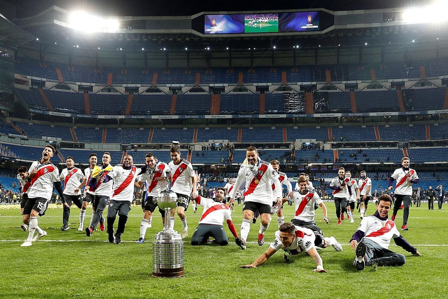 Ecstatic River Plate players celebrating after beating fierce rivals Boca Juniors 3-1 in the second leg of the Copa Libertadores final in Real Madrid's Santiago Bernabeu stadium. The second leg was moved from Argentina after a violent attack on Boca'