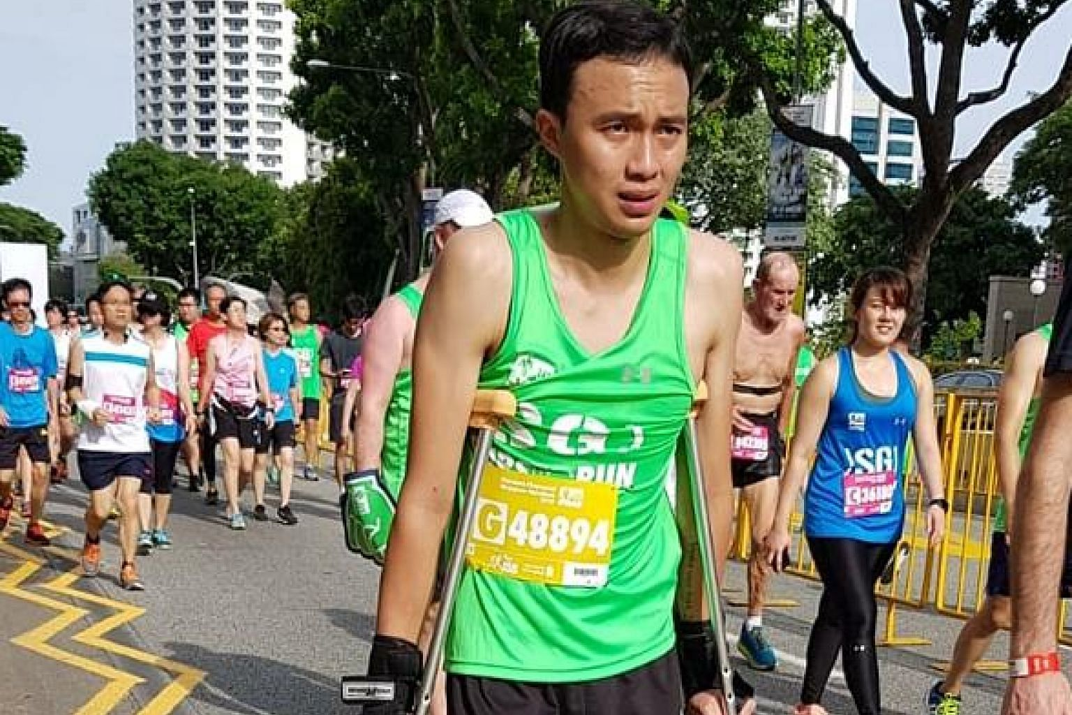Yeoh Lai Tsin, 22, doing the 5km at last Saturday's Singapore Marathon on crutches, with a piece of paper pinned to his vest seeking donations for Yemen and listing the website of the World Food Programme.