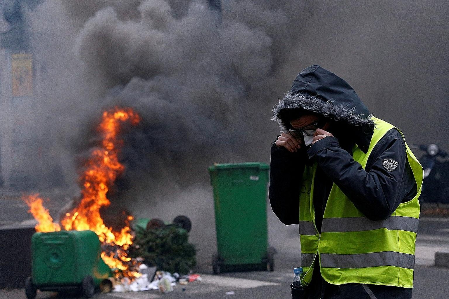 A yellow vest protester near burning trash bins during clashes with police in Paris last Saturday. Protesters across France were galvanised by a plan to raise fuel taxes, but are now demanding, among other things, default on the public debt, exit fro