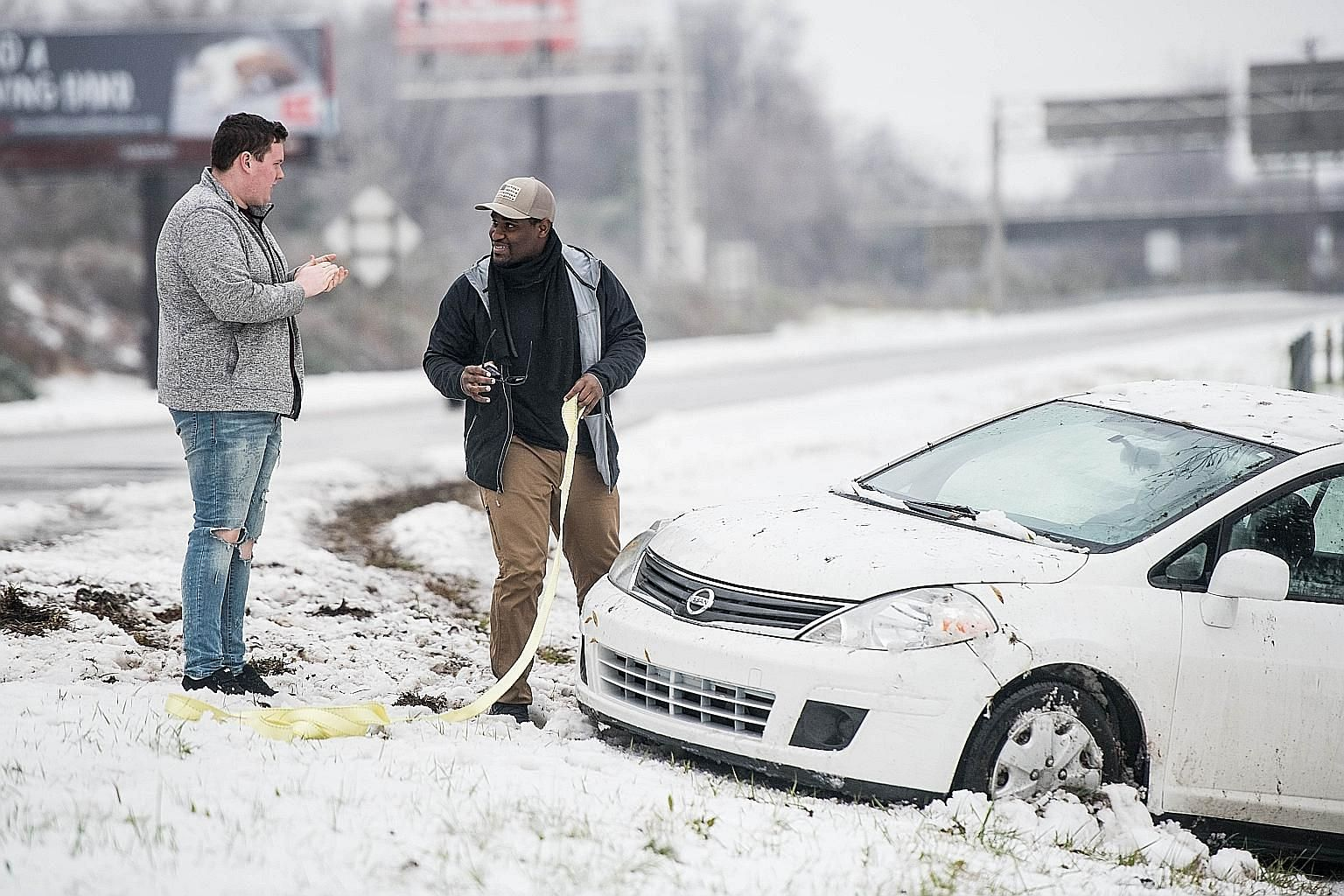 Two men preparing to pull a vehicle out of the snow after a motorist slid off the road on Sunday in Charlotte, North Carolina. The governor's office there said one person died from a heart condition while en route to a shelter and another person died