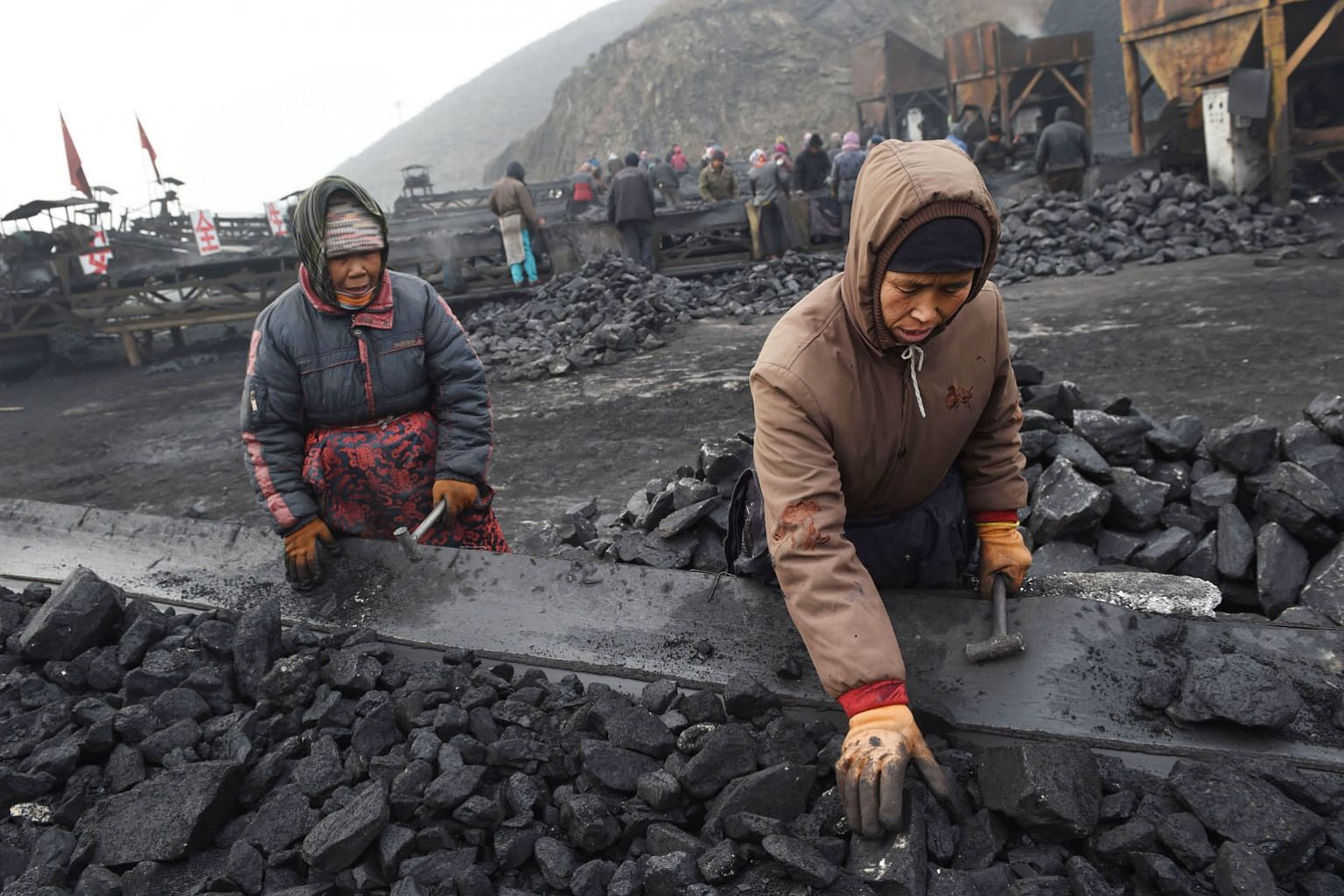 Workers sorting coal near a mine in Datong, in China's northern Shanxi province, in 2015. China has pledged to begin decreasing its use of coal by 2030, among other measures, but the writer says it can do more such as stopping its financing and build