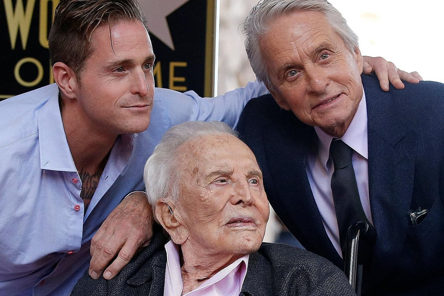 Veteran actor Kirk Douglas (centre) at the unveiling of the Hollywood Walk of Fame star of his son, Michael (right), last month. With them is Michael's son Cameron.