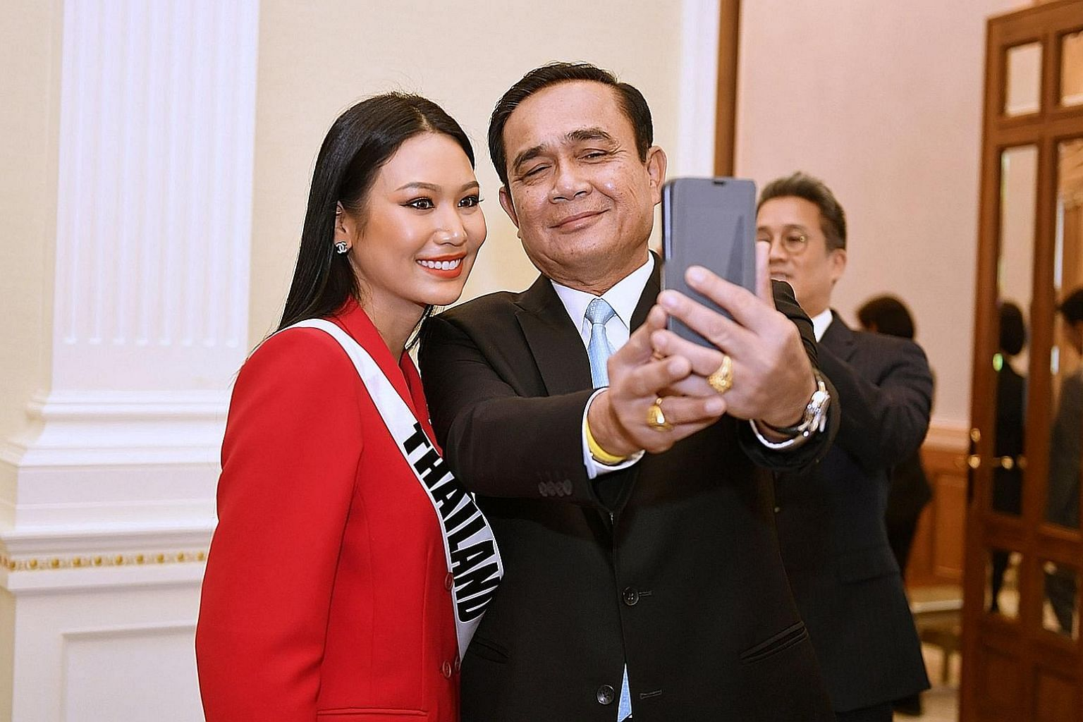 Thai Prime Minister Prayut Chan-o-cha taking a selfie with Thailand's Miss Universe 2018 contestant Sophida Kanchanarin after a meeting at Government House in Bangkok on Tuesday. Some politicians say having Mr Chan-o-cha return as premier would give