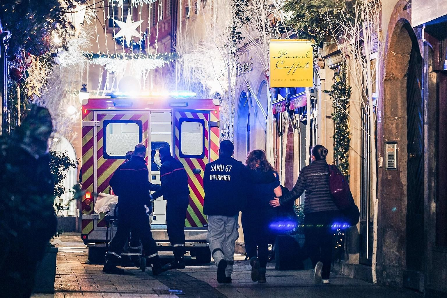 (Top) Paramedics treating an injured person on a street in Strasbourg after the shooting on Tuesday. (Above) French special police force members patrolling the French-German border yesterday. Emergency workers escort a woman after the shooting near t