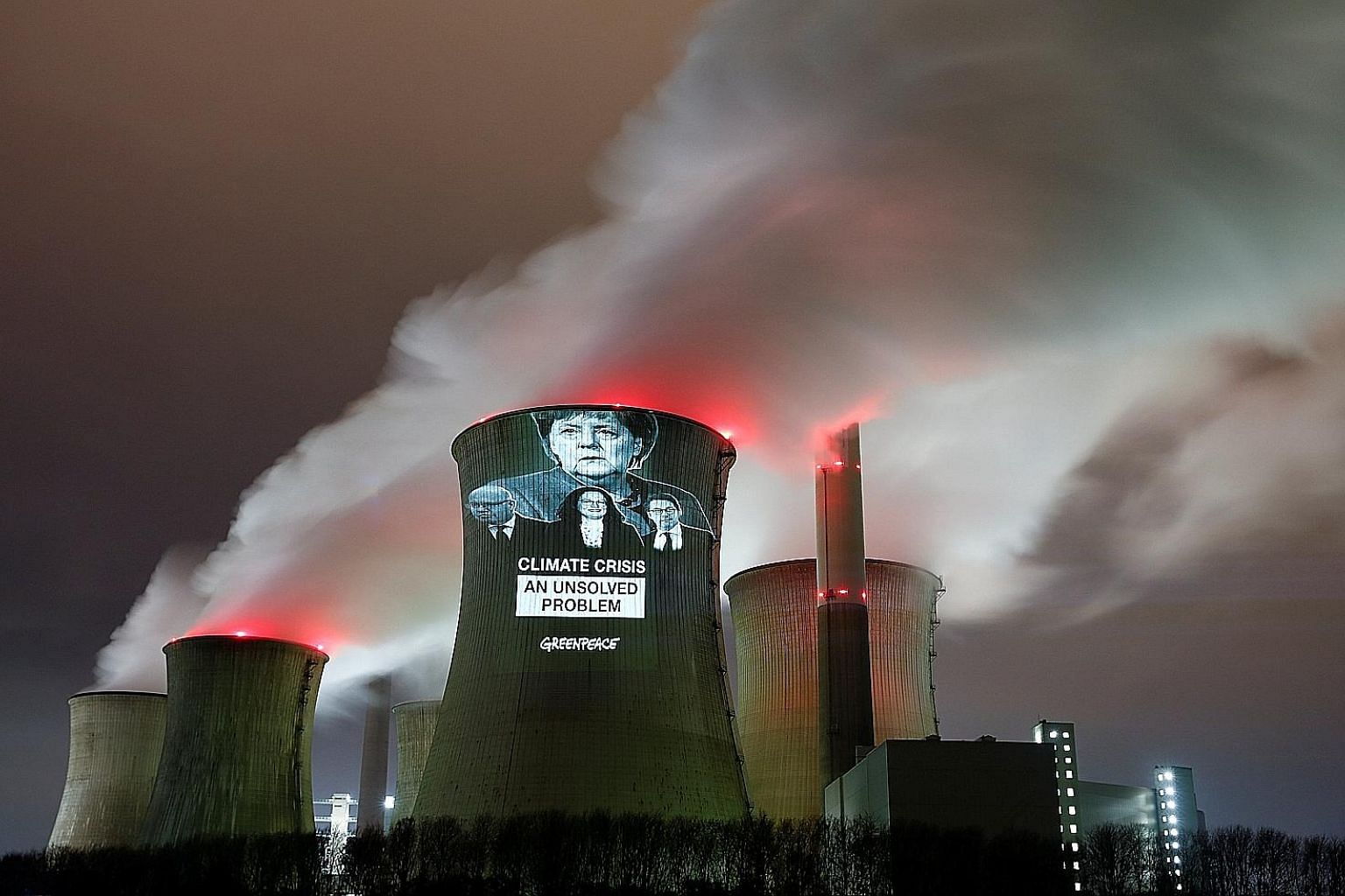 Images of German Chancellor Angela Merkel (top), and (from left) German Economy Minister Peter Altmaier, Social Democratic Party chairman Andrea Nahles and German Transport Minister Andreas Scheuer projected by Greenpeace activists on a cooling tower