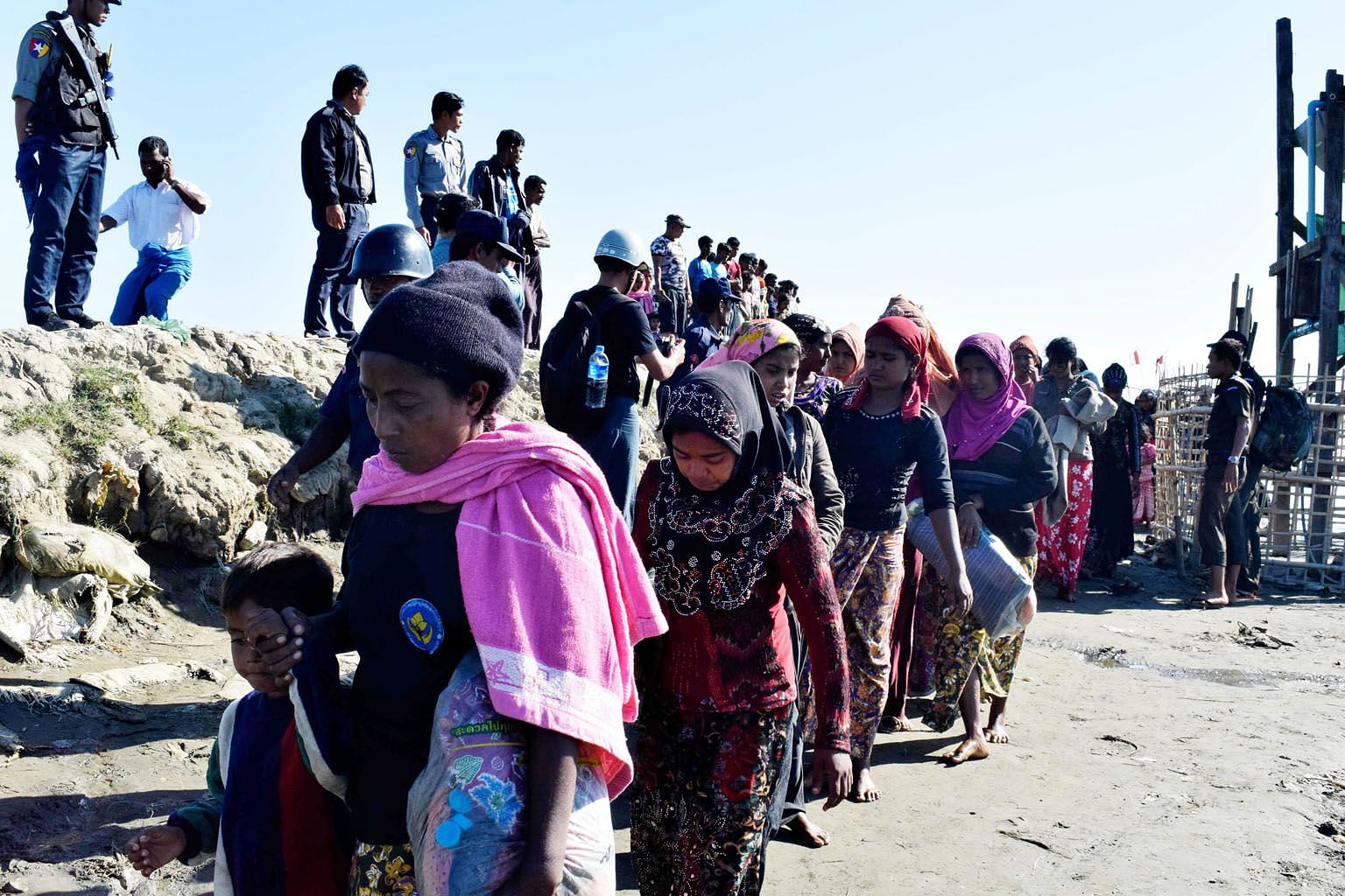 """Myanmar navy personnel escorting Rohingya Muslims back to their camp in Sittwe, Rakhine state, on Nov 30. The US' Lower House of Congress also accuses the Myanmar military of """"crimes against humanity""""."""