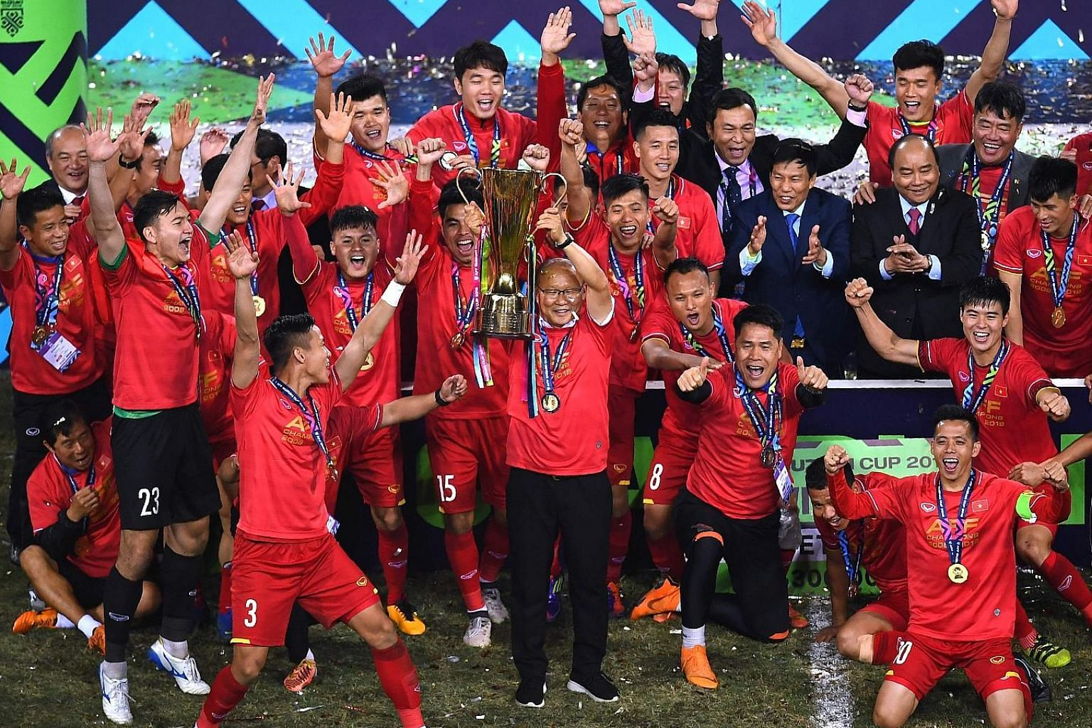 Vietnam's coach Park Hang-seo (centre) holding the trophy as the players and Vietnamese Prime Minister Nguyen Xuan Phuc (second from right in black suit) celebrate after winning the AFF Suzuki Cup last night. Vietnam defeated Malaysia 1-0 (3-2 on agg