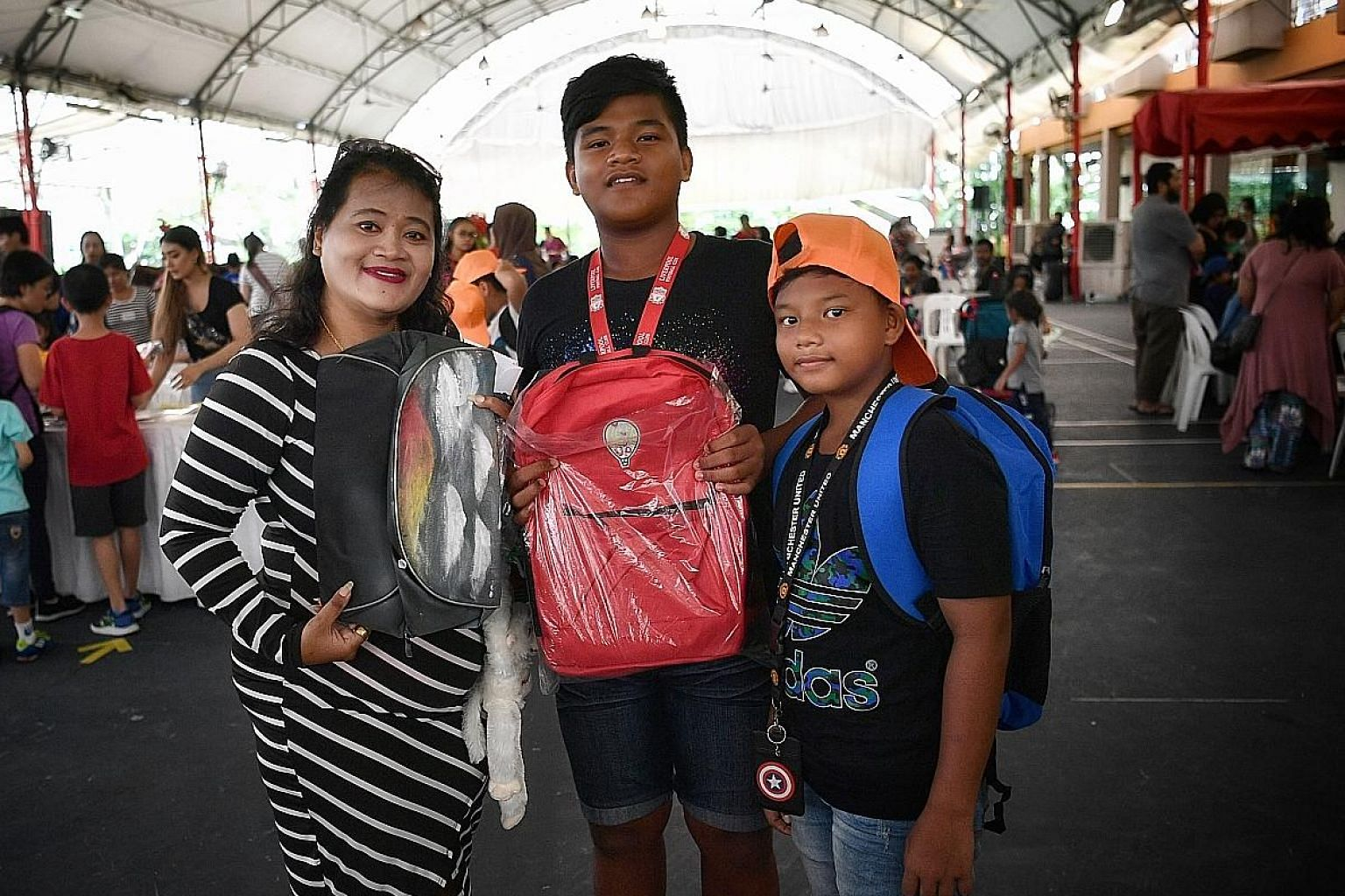 Madam Animaton Mohd Tahil and two of her sons, Mohammad Danial, 13, and Mohammad Diniy, 11. The boys were among 166 students who received support under the Pack My Backpack initiative.