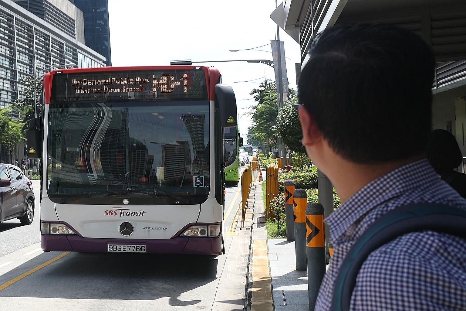 Journalist Zhaki Abdullah (left) booked an on-demand public bus in the Marina Bay area using the BusNow app yesterday, while Mr Low Chong Gee (below), 50, a shipping agent, tried out the same app.