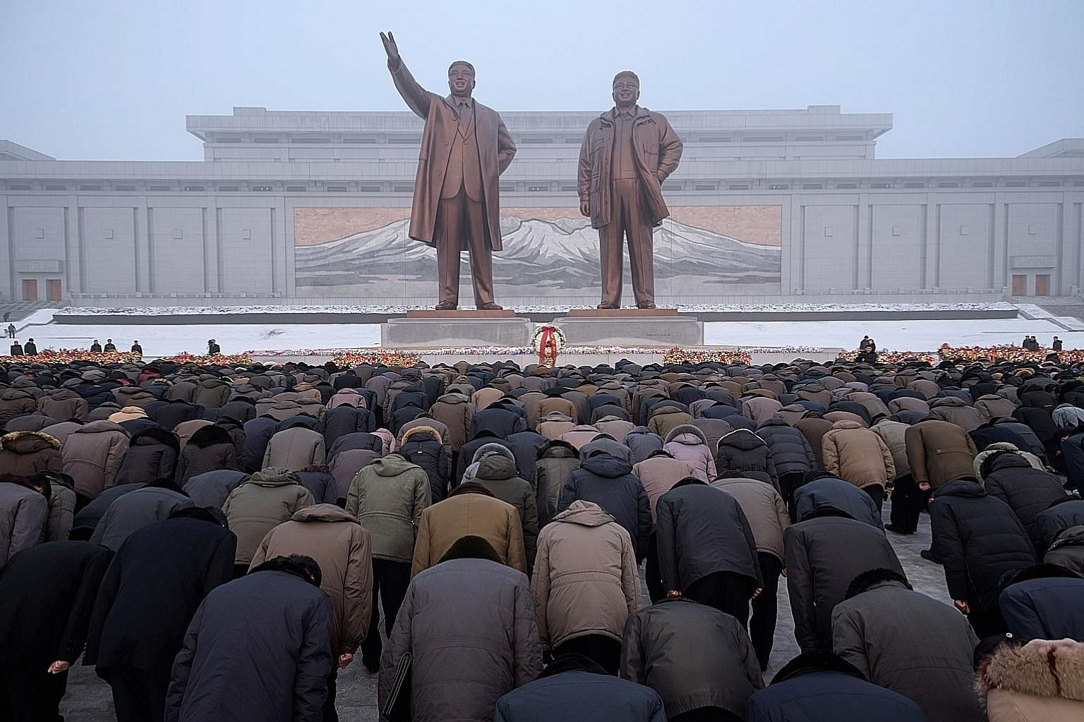 Pyongyang residents bowing before the statues of late North Korean leaders Kim Il Sung (far left) and Kim Jong Il during National Memorial Day on Mansu Hill in Pyongyang yesterday. North Korea marked the seventh anniversary of the death of Mr Kim Jon