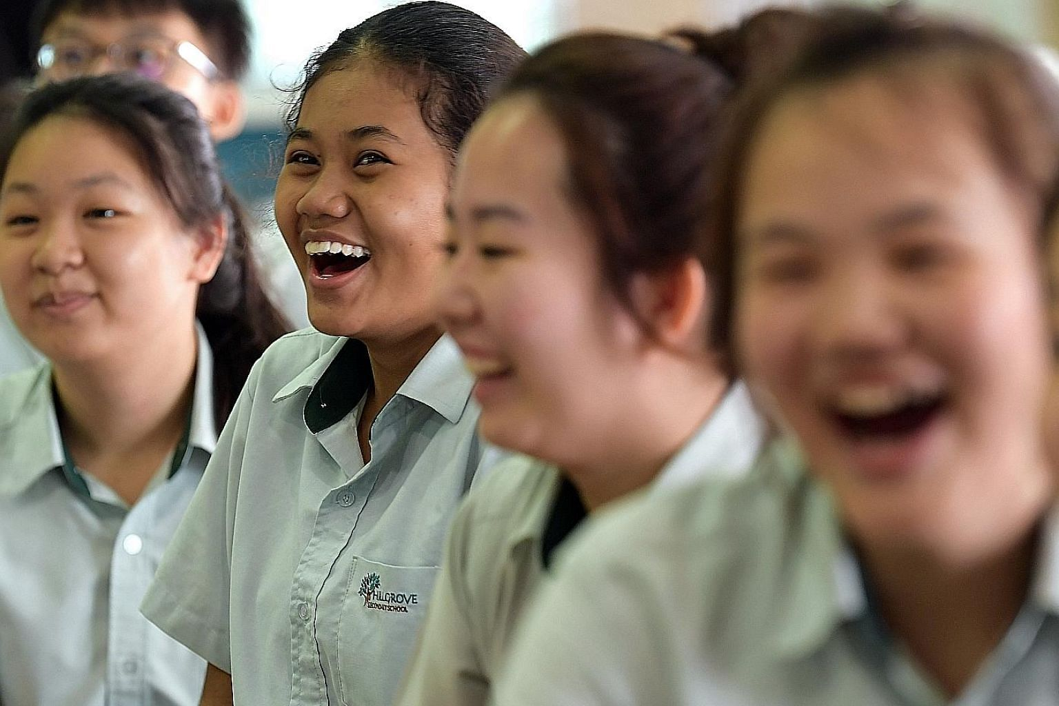 Hillgrove Secondary School student Nur Syafiqah Dahlan (second from left) and her schoolmates reacting to news of their school's performance in the N-level exams yesterday. She qualifies for Sec 5 and for Higher Nitec courses at the ITE. Principal An