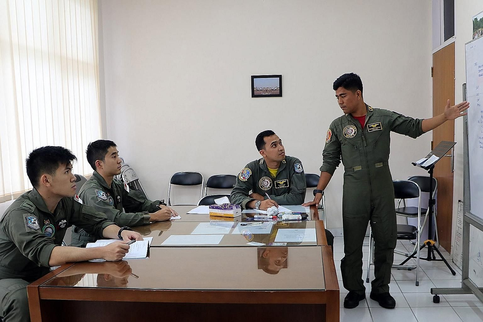 Above: RSAF and TNI AU personnel conducting mission planning together before the flight. Left: The RSAF's F-16C and TNI AU's Hawk 209 taking part in a mission during Exercise Elang Indopura 2018.