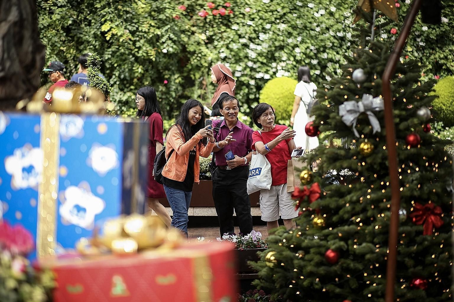 Mr Fok Hup Seng, a hospital cleaner, touring the Christmas display at the Flower Dome in Gardens by the Bay yesterday with his daughter Xin Yi and sister Hup Yee, 66, a retiree. They were among 350 lower-income union members and their families at an