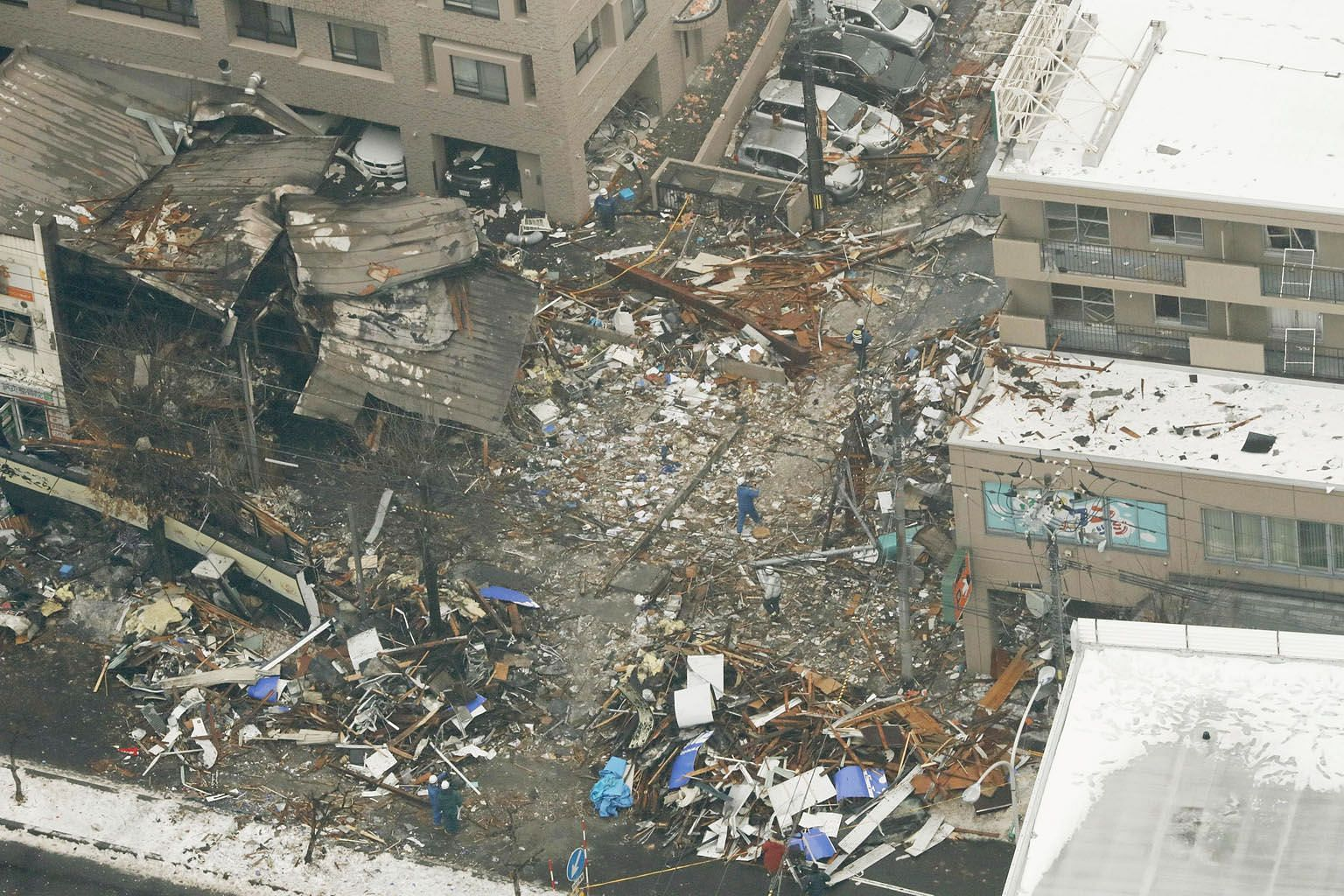This aerial view shows workers inspecting the site of the collapsed and charred building in Sapporo, northern Japan, where a large explosion occurred, injuring 42 people. The force of the explosion shattered glass windows in at least 20 buildings, so