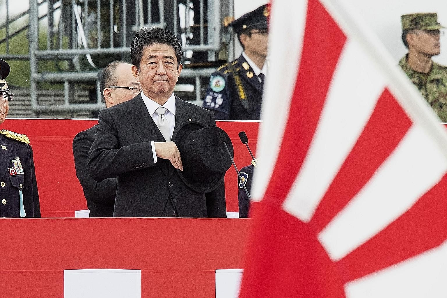 Japanese Prime Minister Shinzo Abe saluting Self-Defence Forces troops in a parade in October. Japan's Cabinet has approved the country's first aircraft carriers since World War II by retrofitting two helicopter destroyers.