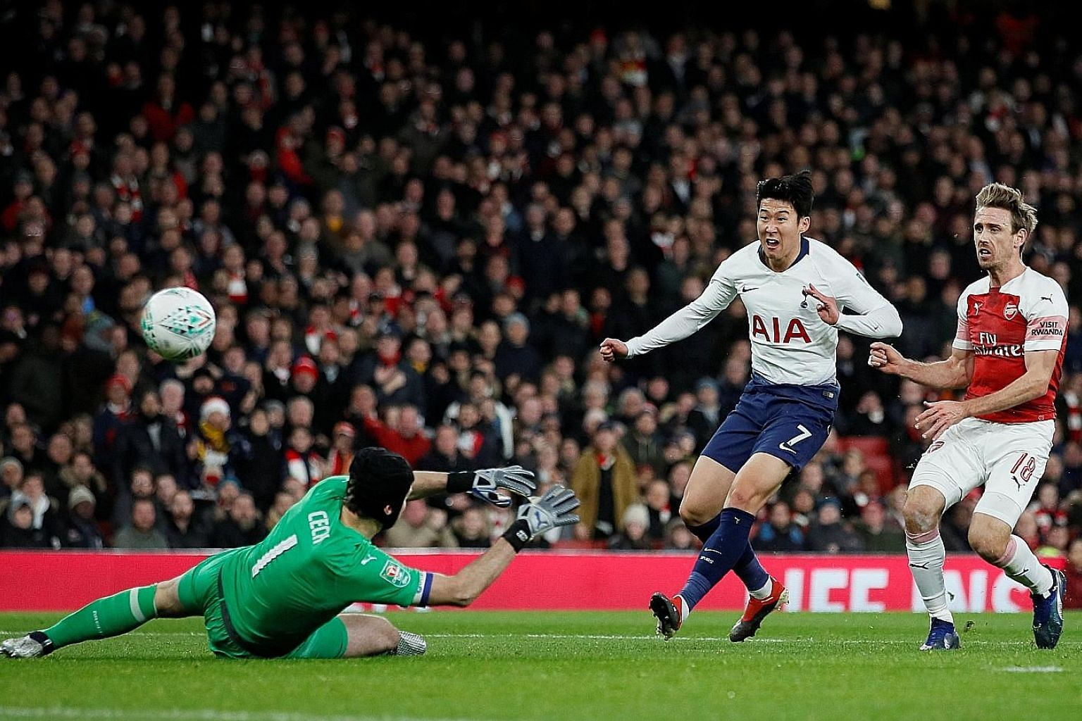 Above: Son Heung-min scoring past Arsenal goalkeeper Petr Cech to put Tottenham in the lead in their League Cup quarter-final at the Emirates Stadium. Left and below: Spurs' Dele Alli being led away by the Gunners' Sokratis Papastathopoulos after bei