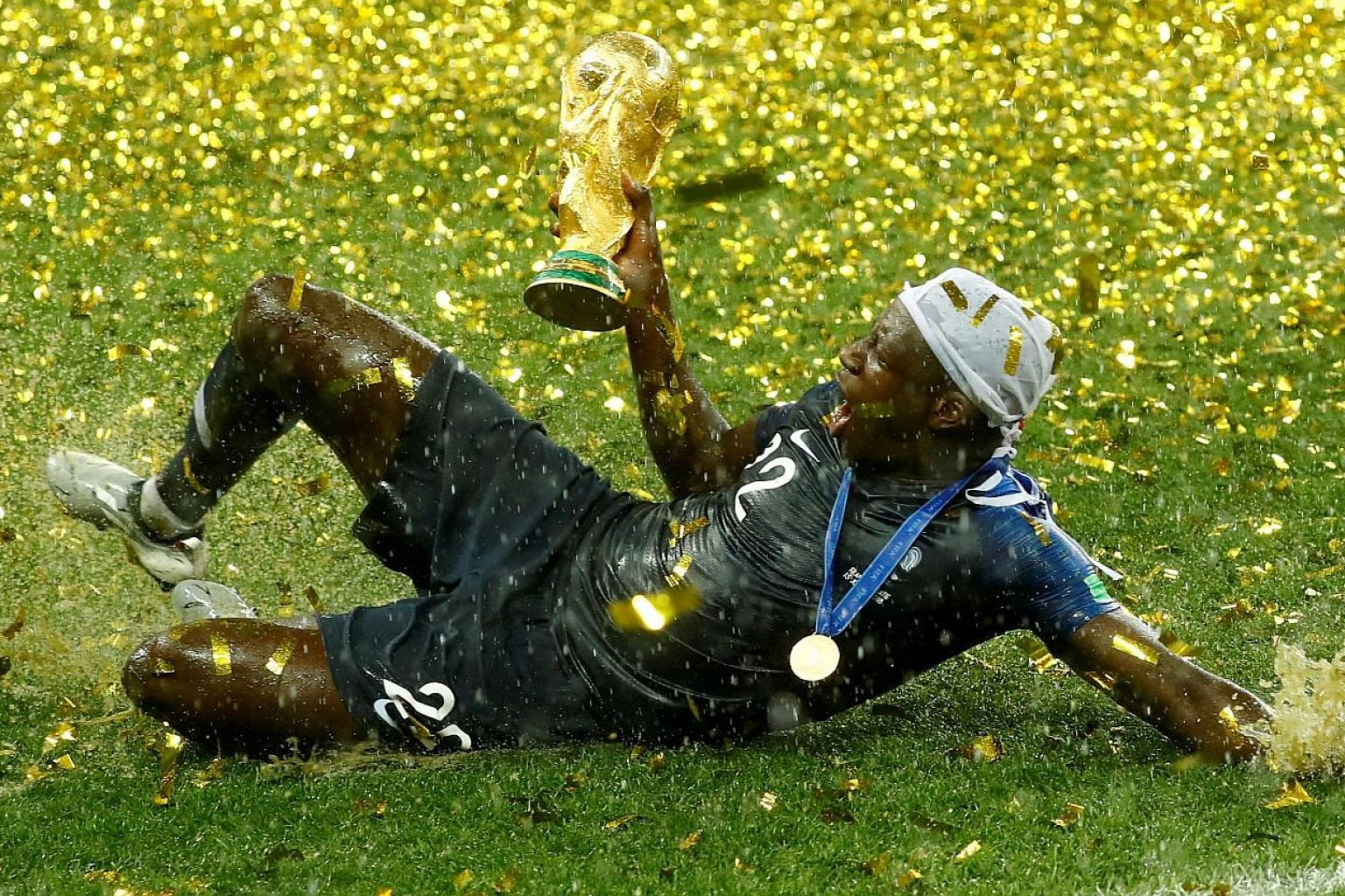 France defender Benjamin Mendy could not contain his joy in the rain as he lifts the World Cup trophy after Les Bleus beat Croatia 4-2 in the final on July 15.