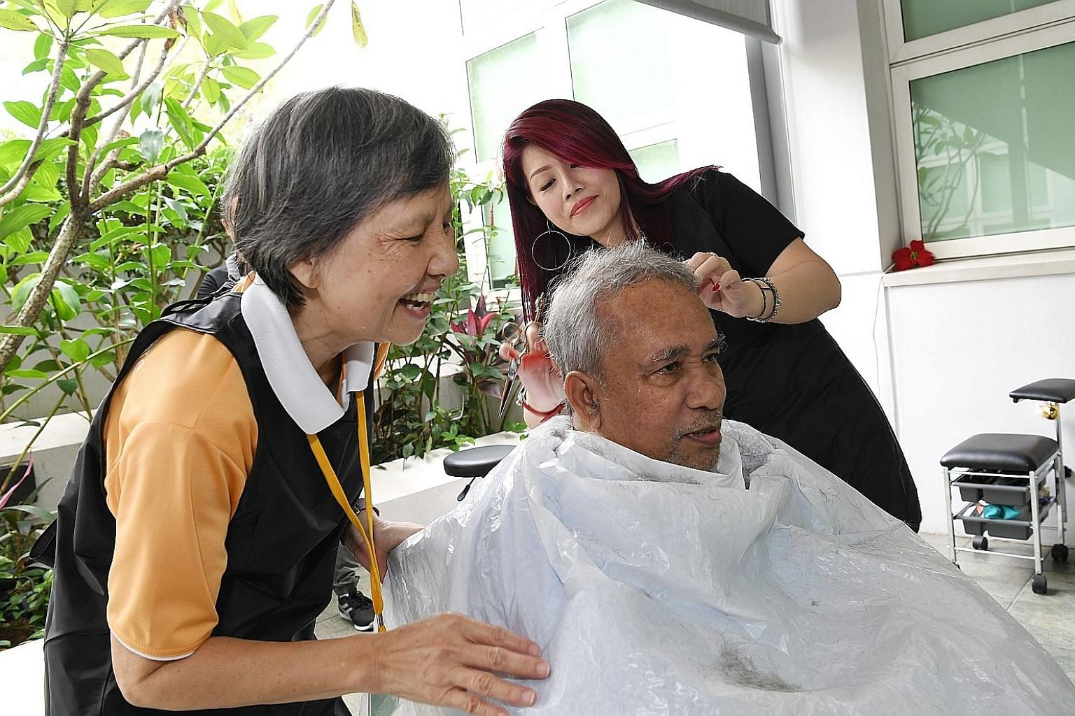 Volunteer Susan Law, 69, keeping patient Syed Mohammed, 66, entertained while hairstylist Doreen Liew, another volunteer, cuts his hair during the basic hair-cutting service for patients of Bright Vision Hospital. From next month, pop-up salons like