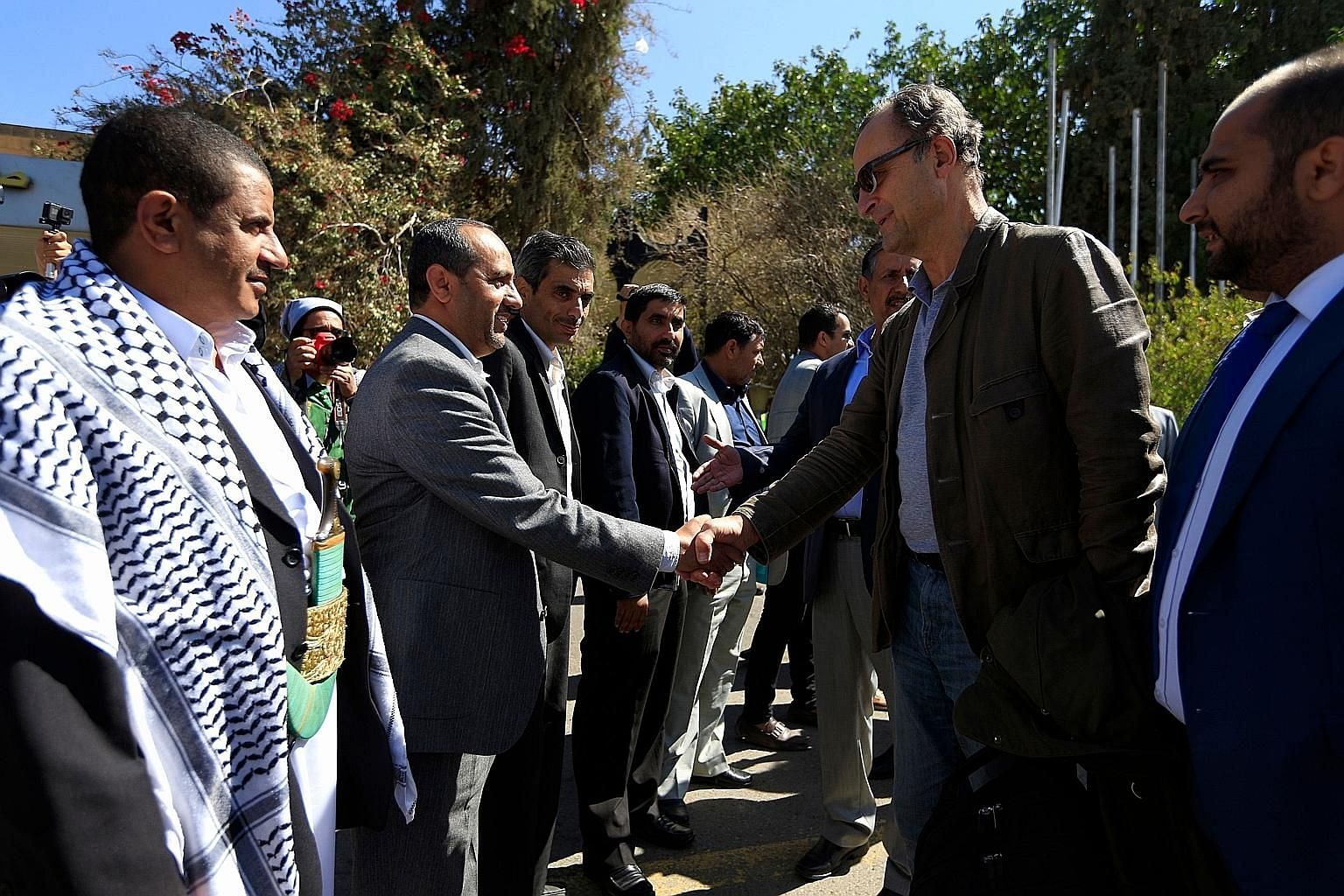 Retired Dutch general Patrick Cammaert (in sunglasses), who heads a UN team monitoring a ceasefire in Yemen's Hodeida, greeting officials upon his arrival in the Yemeni capital Sanaa yesterday.