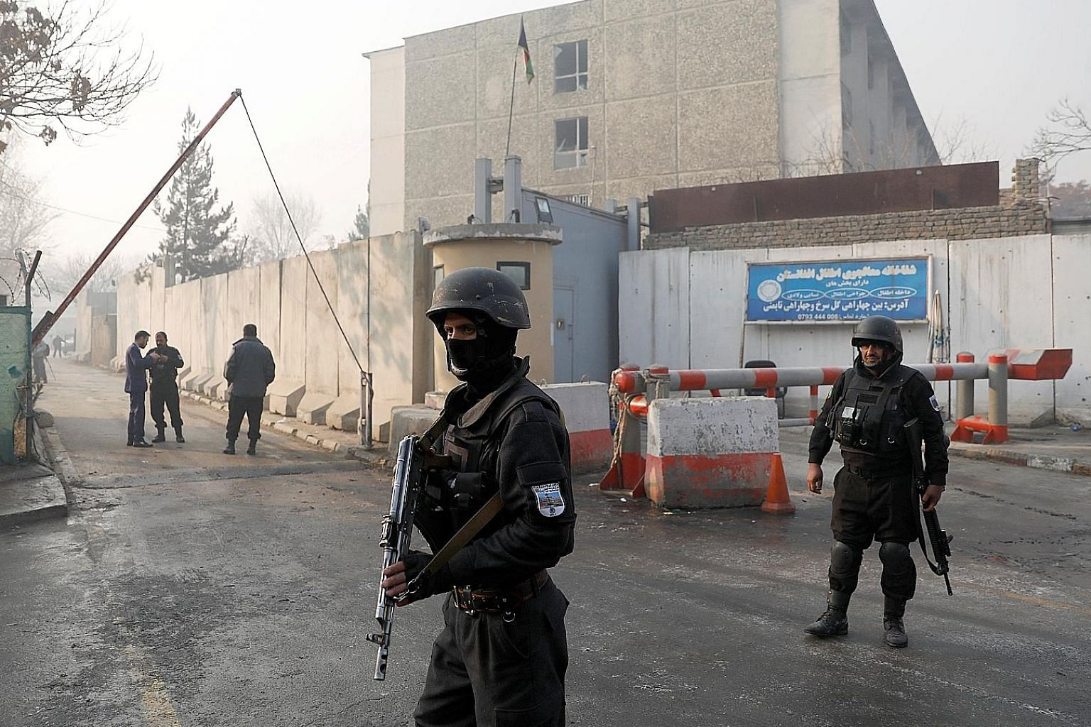 Afghan police officers standing guard outside the government compound in Kabul, after Monday's attack, the first major violent assault in the capital since last month, when a terrorist bomber killed more than 50 people in a hotel.