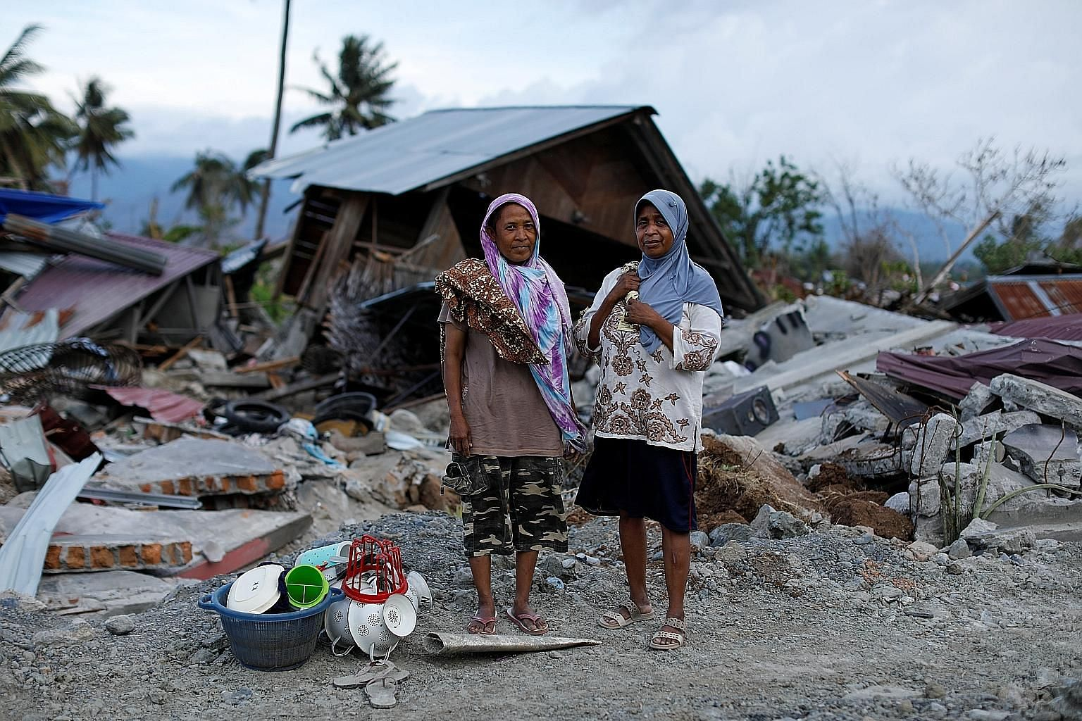 Sisters Sakinah, 49, and Zulfina, 55, with the items they had salvaged from their destroyed home in the Petobo neighbourhood of Palu, in Central Sulawesi, after a tremor-triggered tsunami struck in September.