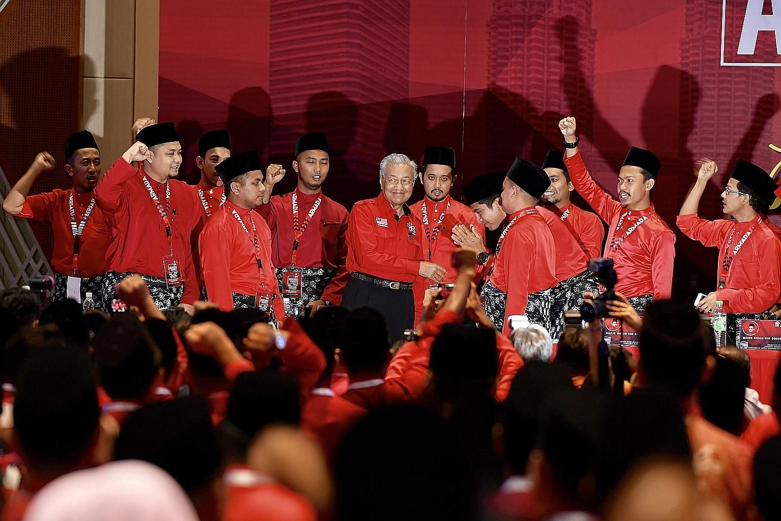 Parti Pribumi Bersatu Malaysia chairman Mahathir Mohamad (centre) being greeted by PPBM Youth leader Syed Saddiq Syed Abdul Rahman and youth delegates at the Putrajaya International Convention Centre yesterday. They were attending a joint session, he