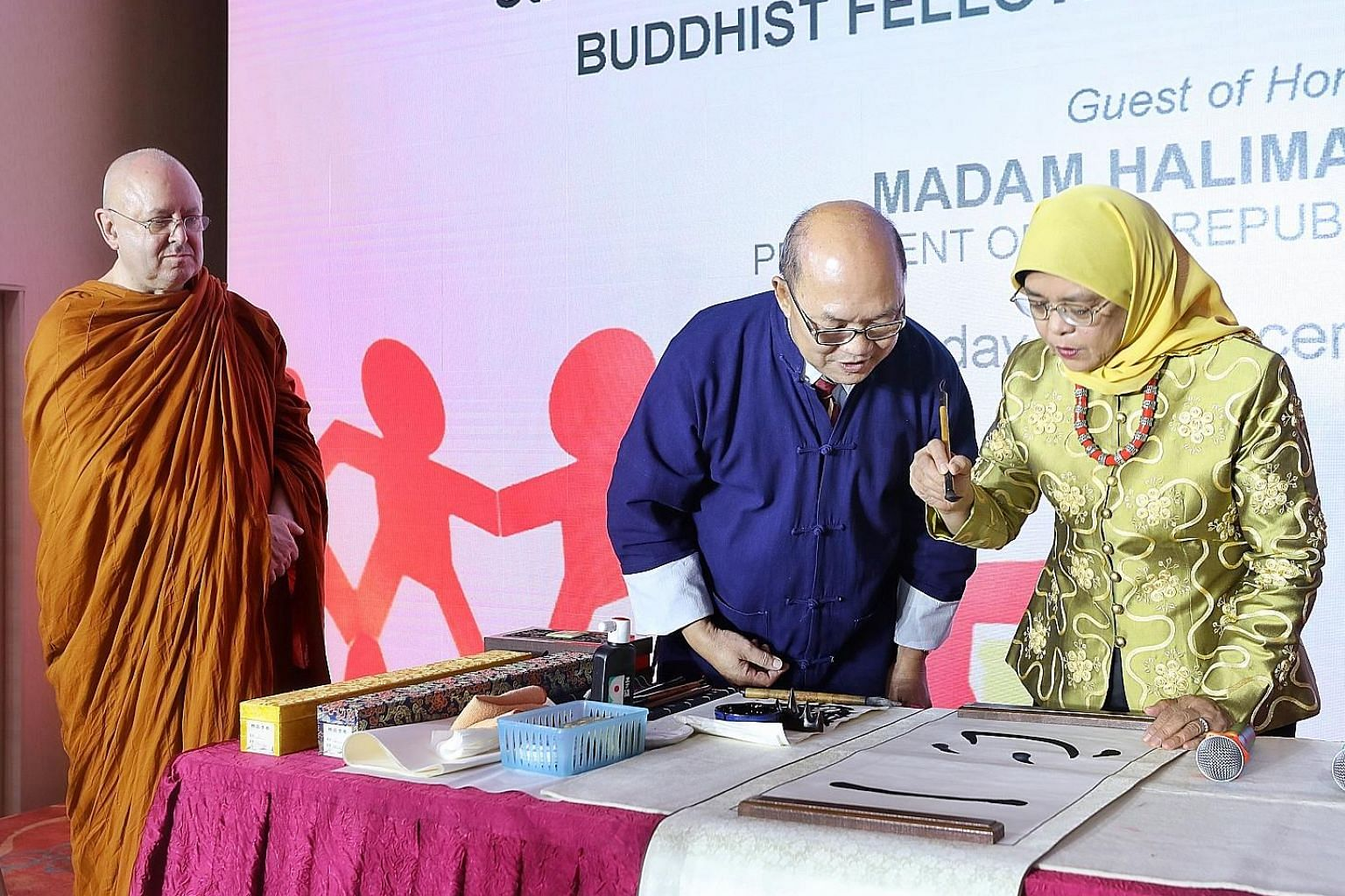 """The phrase """"one heart"""" echoed what Buddhist Fellowship president Lim Phang Hong identified as the key teachings of Buddhism - harmony and togetherness. The event's guest of honour, President Halimah Yacob, penning Chinese calligraphy of the phrase """"o"""