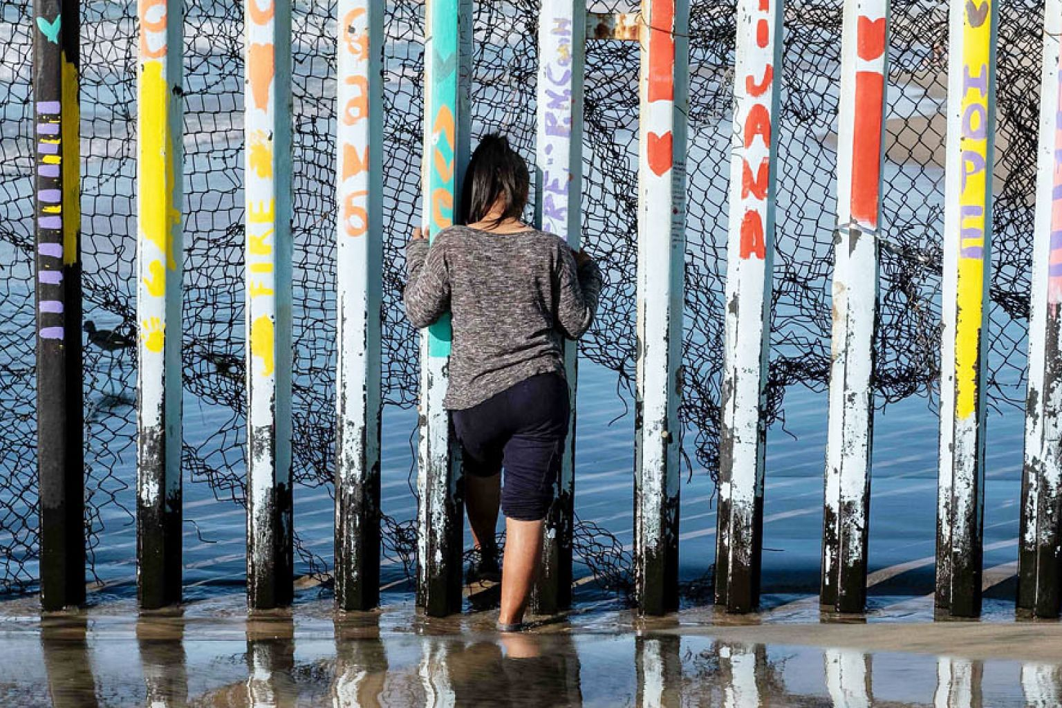 A girl from El Salvador looking through the US-Mexico border fence in Playas de Tijuana, Baja California state, Mexico, hoping, like other Central American migrants, to get into the United States. At the end of 2017, there were nearly 25.4 million refugee