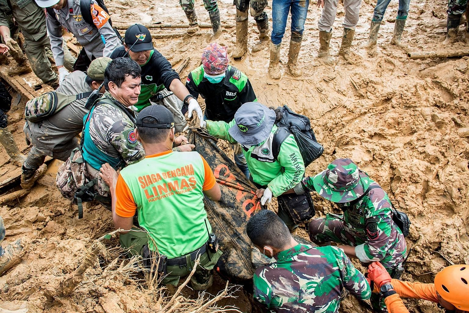 Rescue workers carrying a body bag in Sukabumi, which was hit by a landslide on Monday. At least 15 people had been found dead and 20 people were still missing by Tuesday night, but search and rescue efforts were impeded by four secondary landslides.